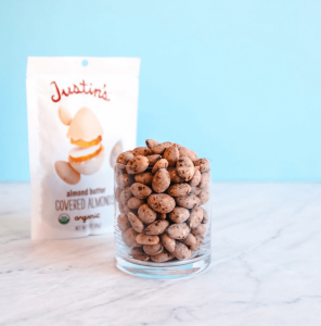 A brightly lit Justin's Almond Butter Covered Almonds in a clear round cup on a white marble tabletop with a light blue wall