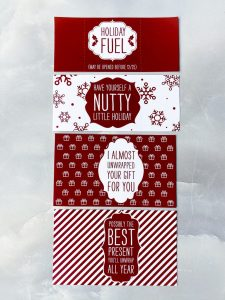 Holiday design sleeves in white and dark red laid out vertically on a stone textured tabletop