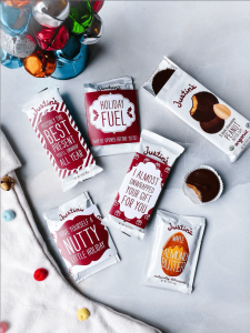 Justin's Nut Butter Cups and Squeeze Packs wrapped in holiday design sleeves beside bucket of bells and Christmas stocking