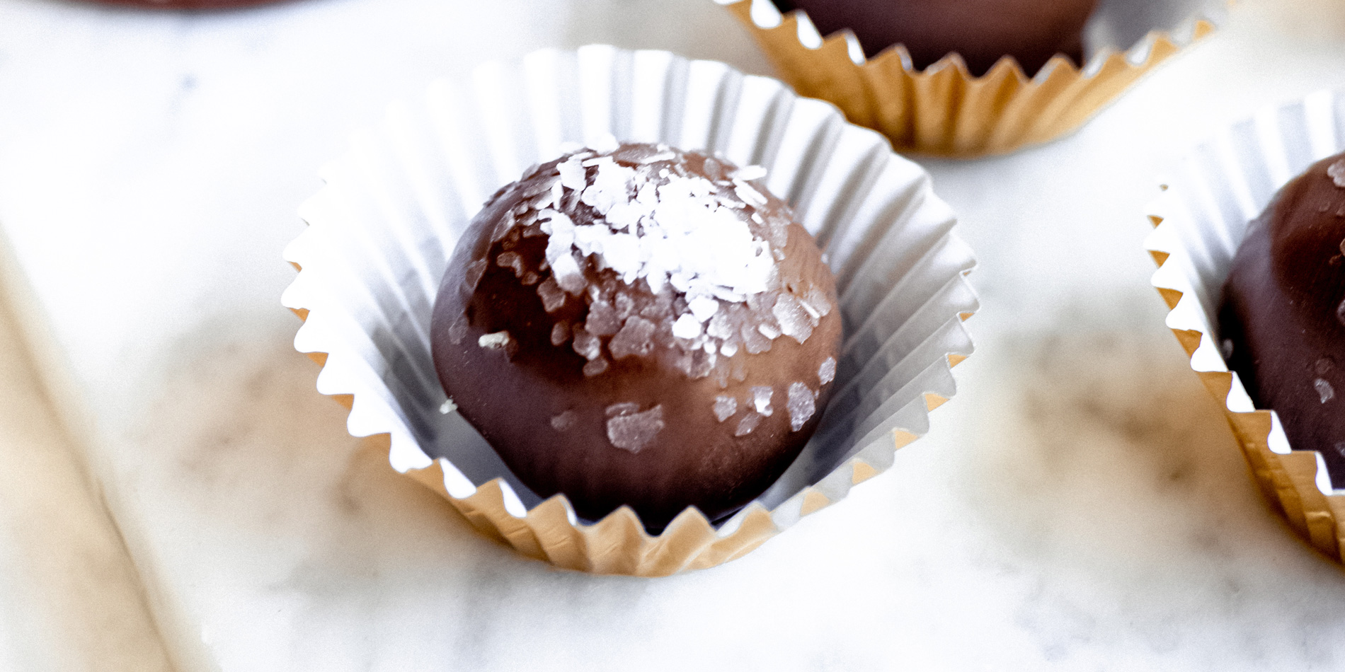 Dark Chocolate Hazelnut and Coconut Truffles in cupcake wrappers on a marble tray on a white background bird's eye view