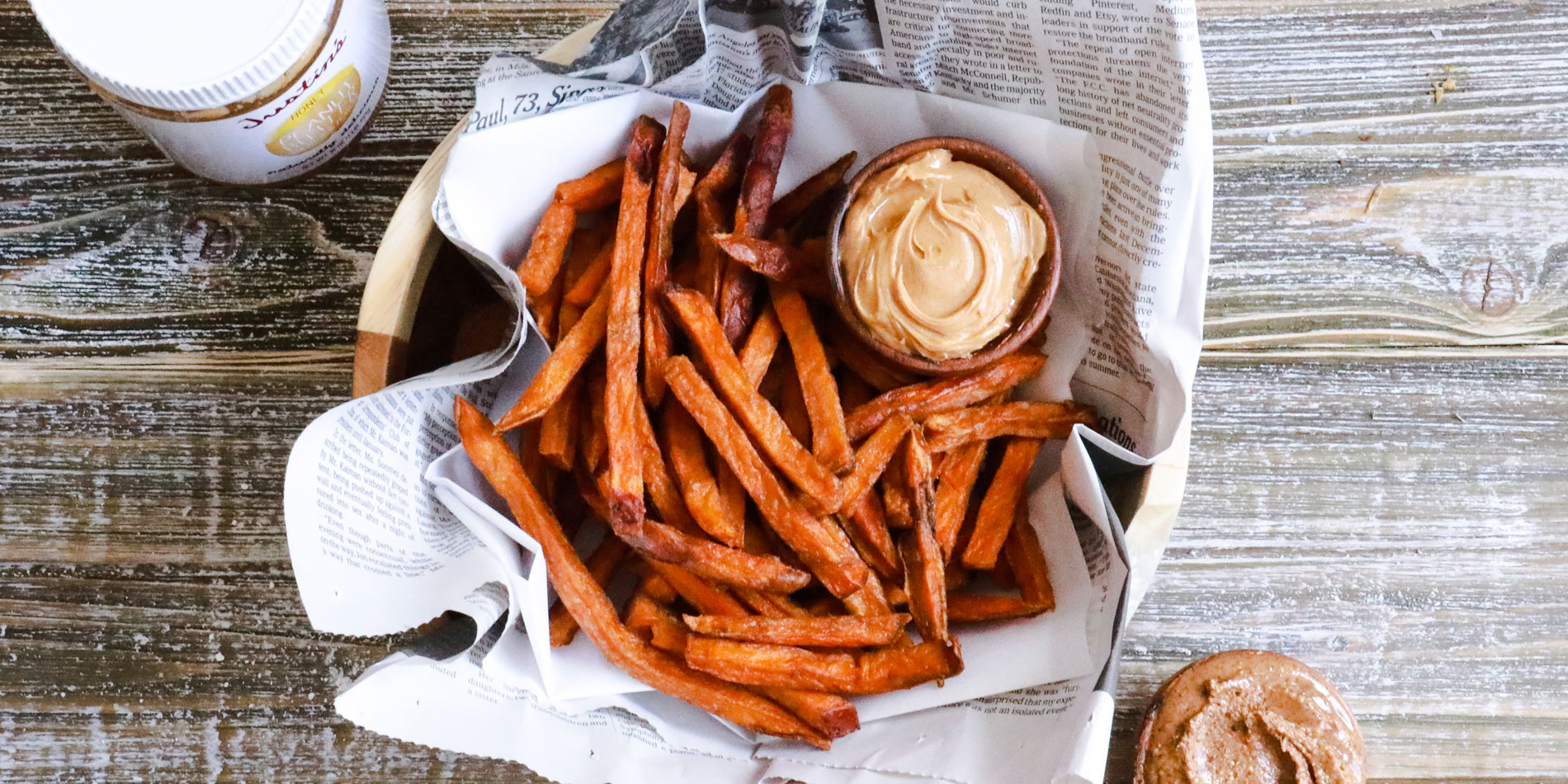 Honey Sweet Potato Fries in parchment paper with Justin's honey peanut butter dip in a wooden bowl and background