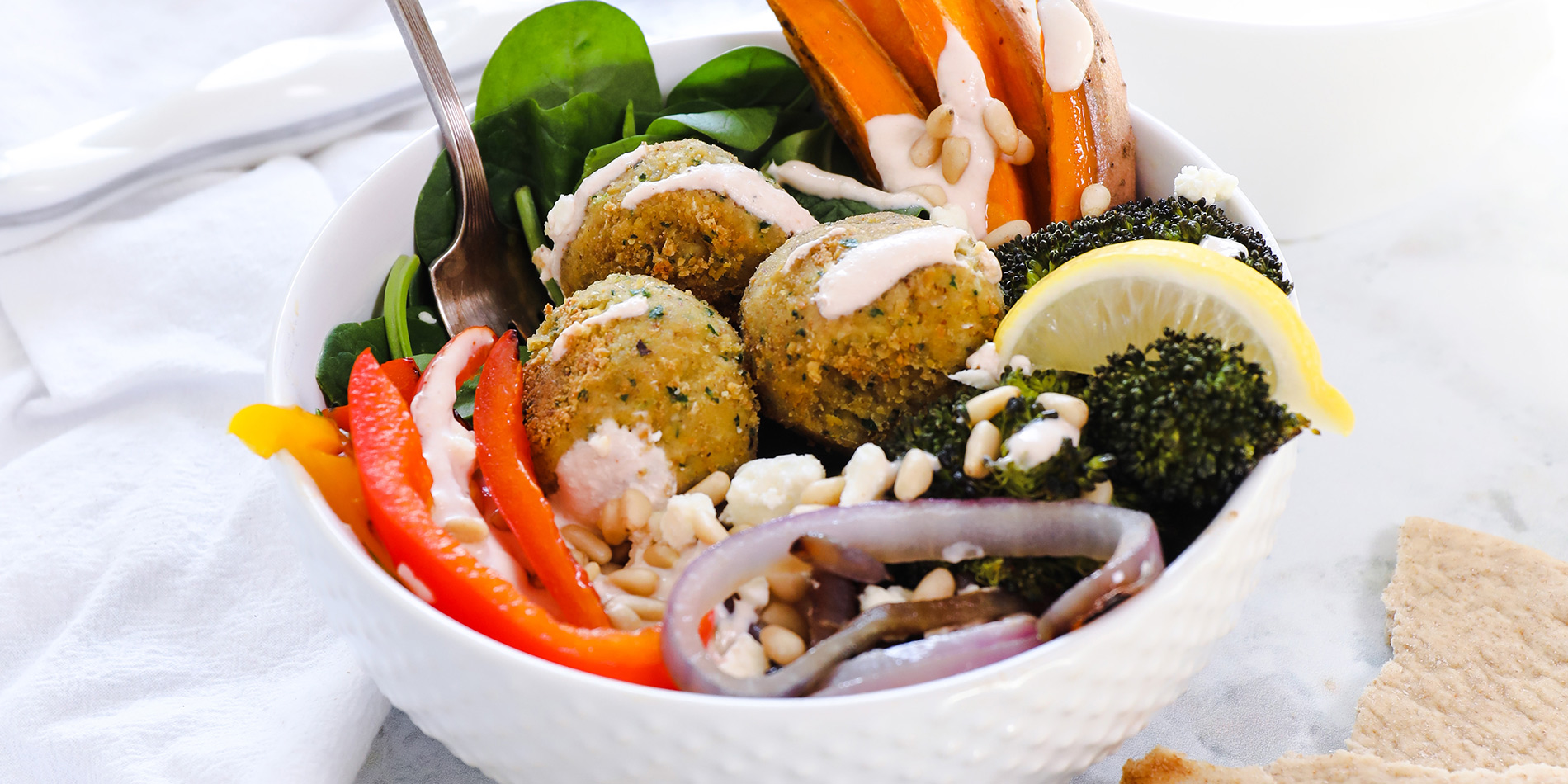 Nutty Falafel sitting in bed of vegetables in a white bowl
