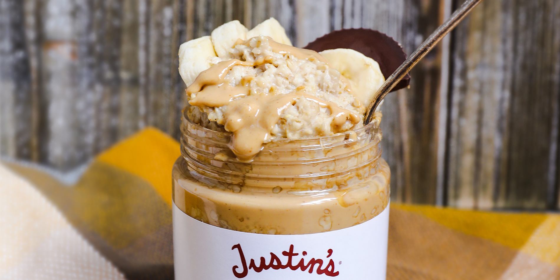 Nutty Overnight Oats in a Justin's Classic Cashew Peanut Butter jar on a blue and brown gingham cloth with a wooden backdrop