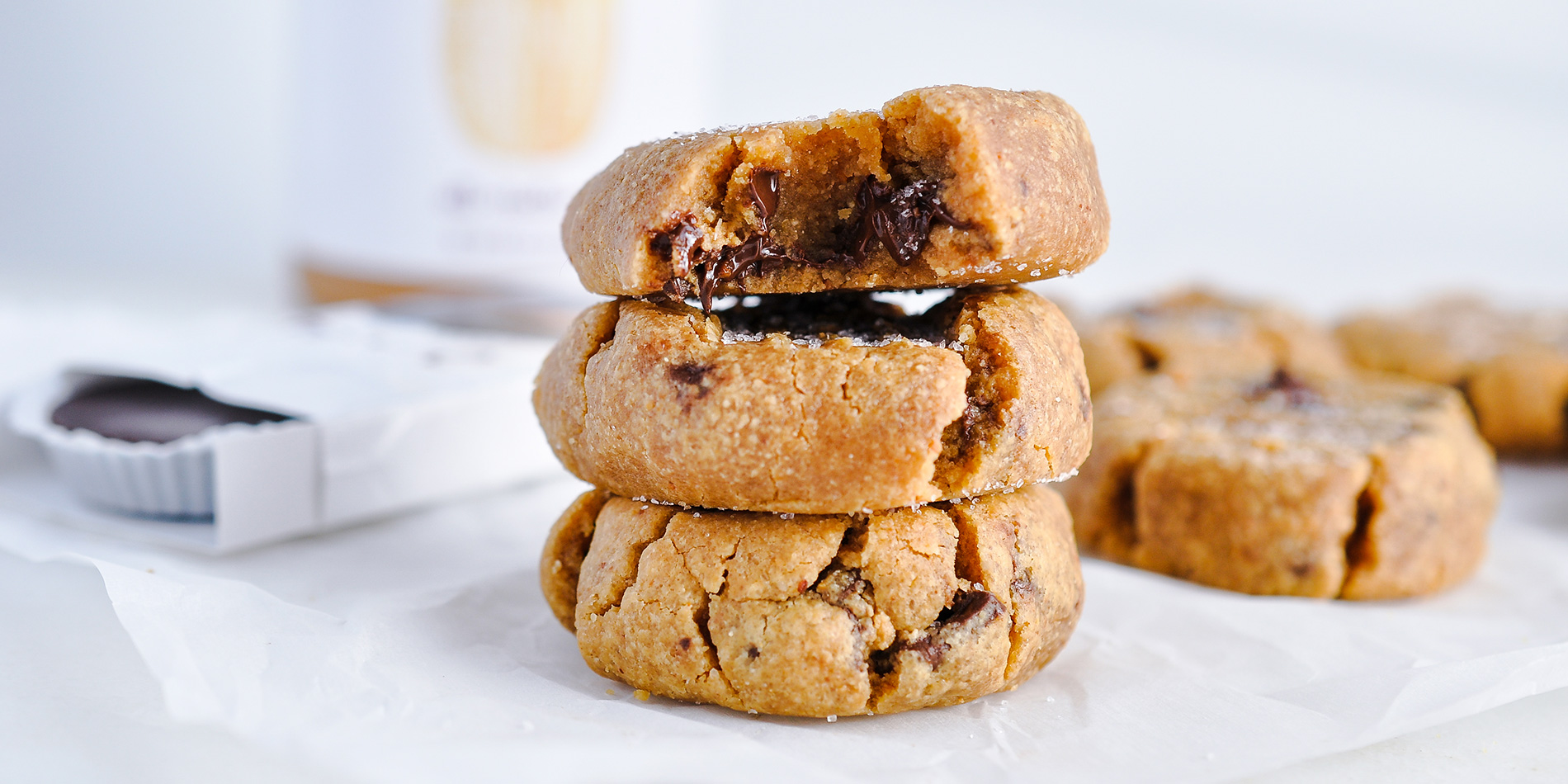 Peanut Butter Cookies stacked with the top one bit revealing the melted chocolate on a white parchment on white background