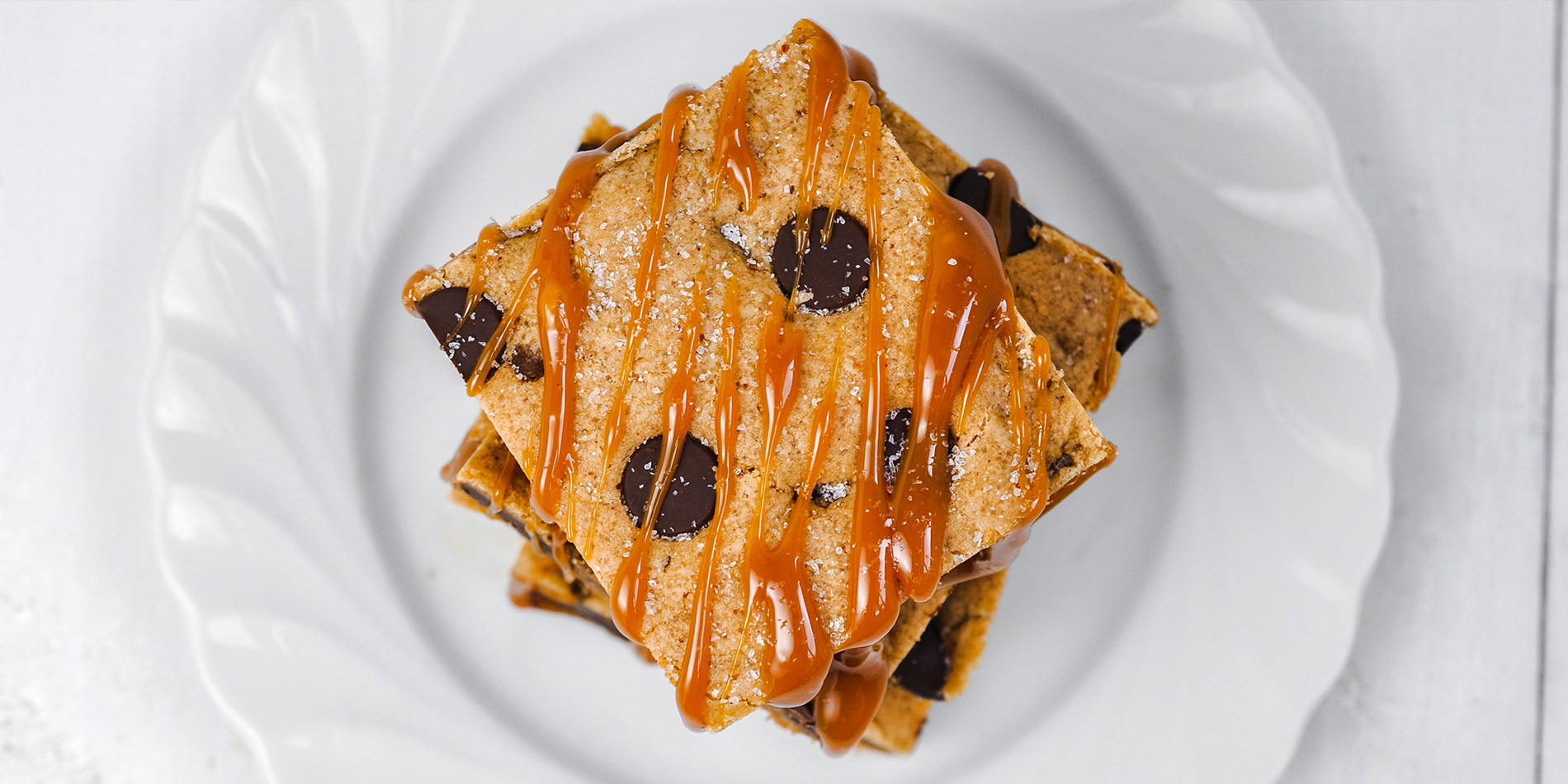 Salted Caramel Chocolate Chip Maple Almond Bars with caramel drizzle on a white plate (bird's eye view) in white background