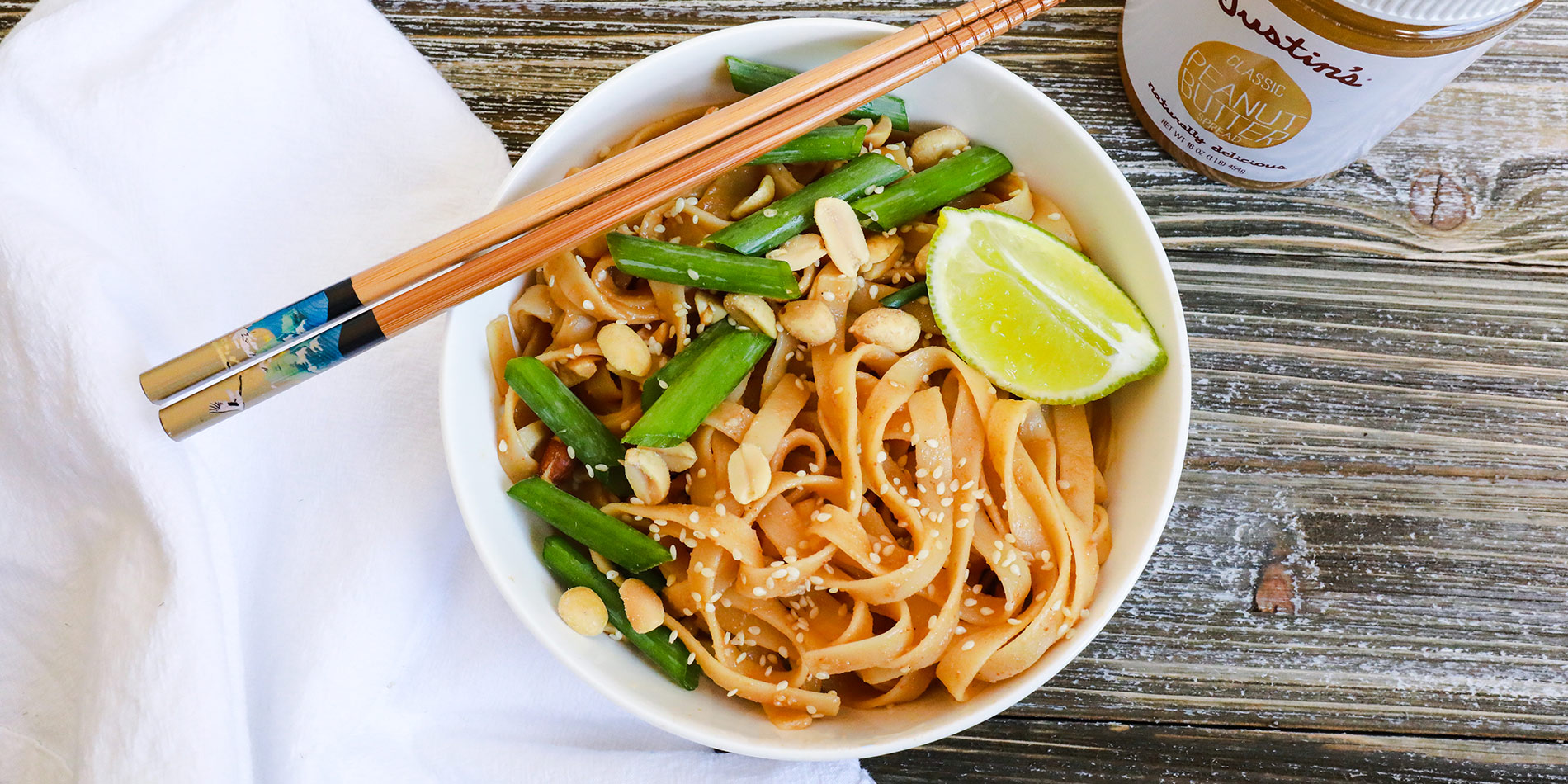 Spicy Peanut Butter Pasta with sesame seeds, peanuts, green onions and a piece of lime on a white bowl with chopsticks.