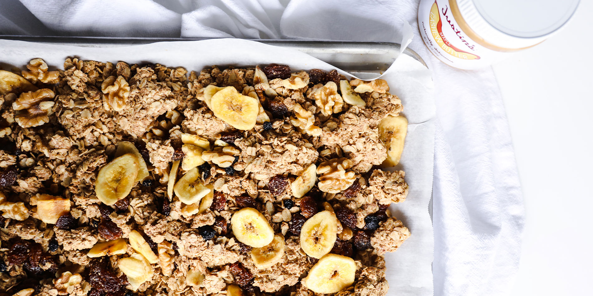 The Best Nut Butter Granola on white parchment sheet in a gray tray which is on a white cloth on a white background