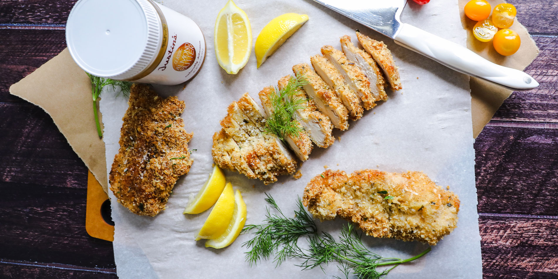 Paleo Almond Butter Crusted Chicken on parchment papers with cut baby tomatoes and lemon slices on a wooden serving tray