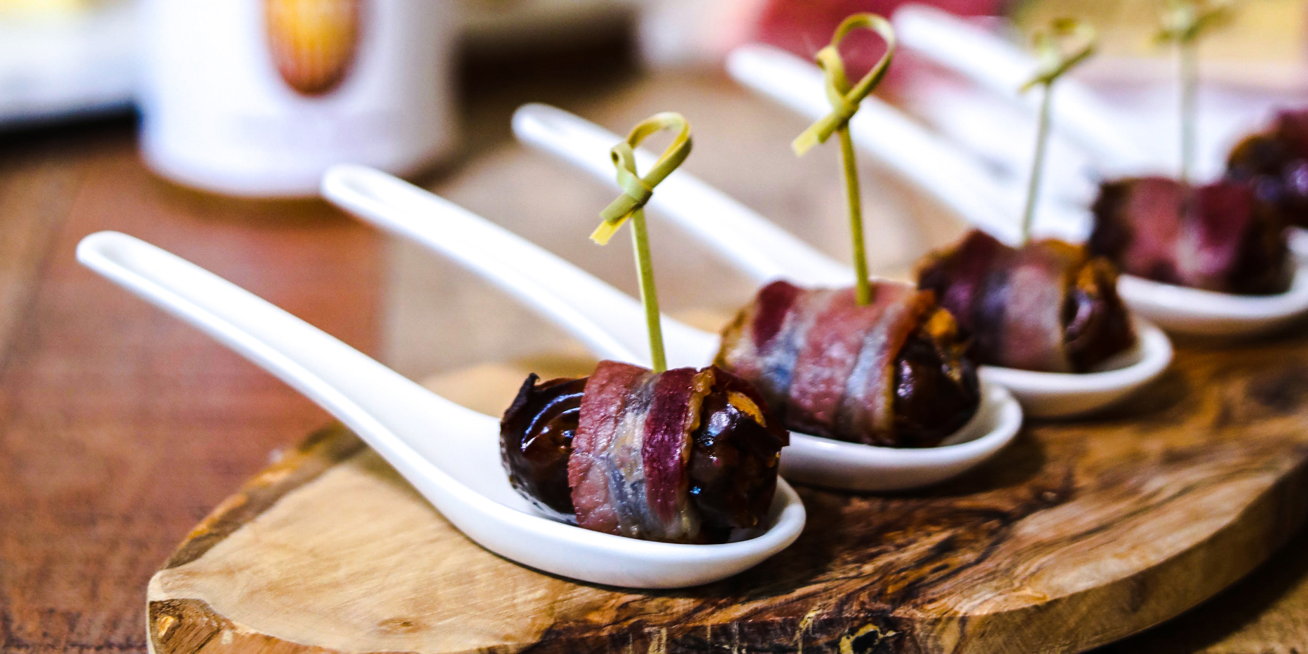 Almond Butter Stuffed Bacon Wrapped Dates on spoons on top of a wooden serving plate on a wood background