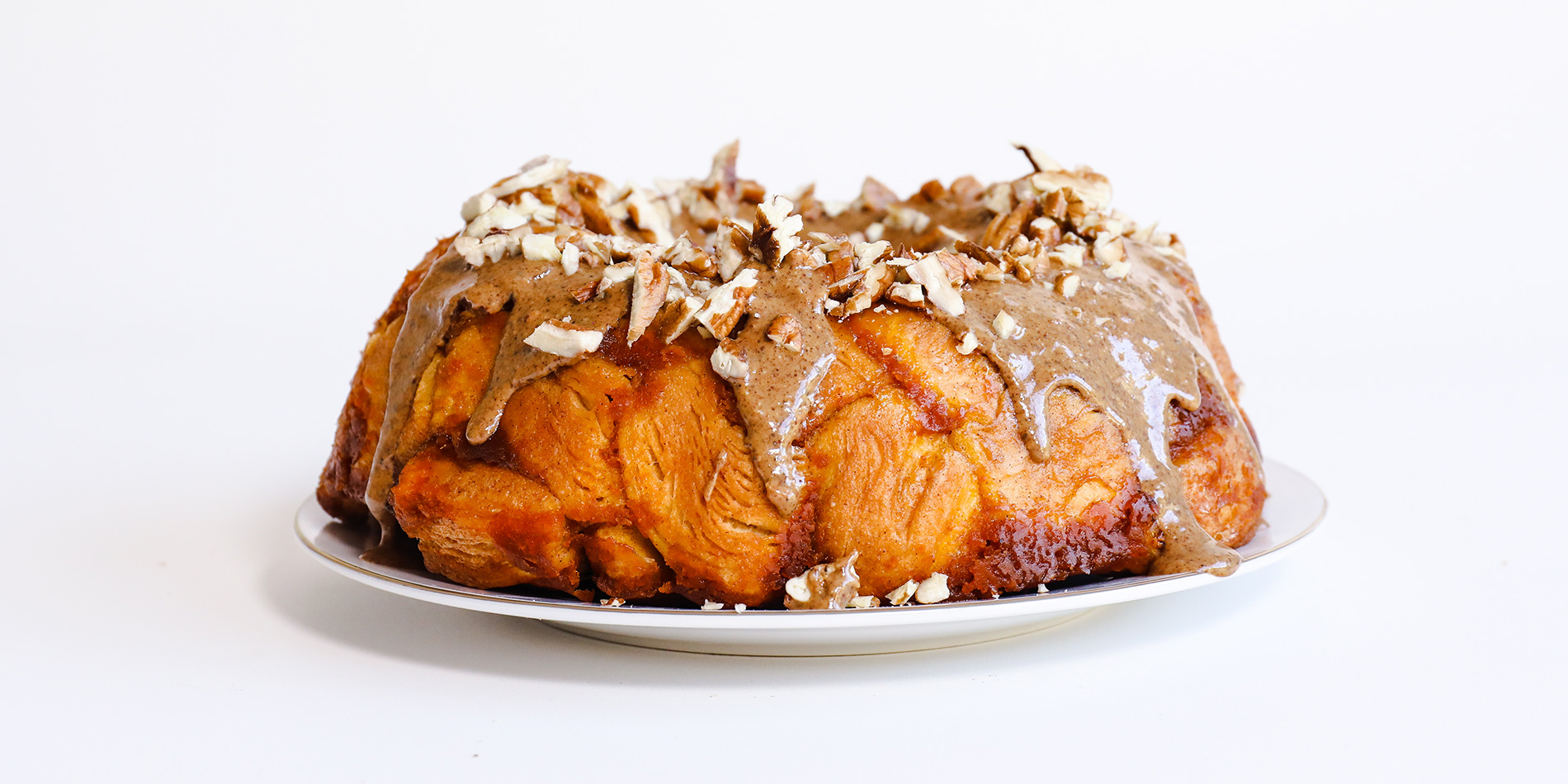 Maple Pumpkin Monkey Bread on a white plate on a white background (side view)