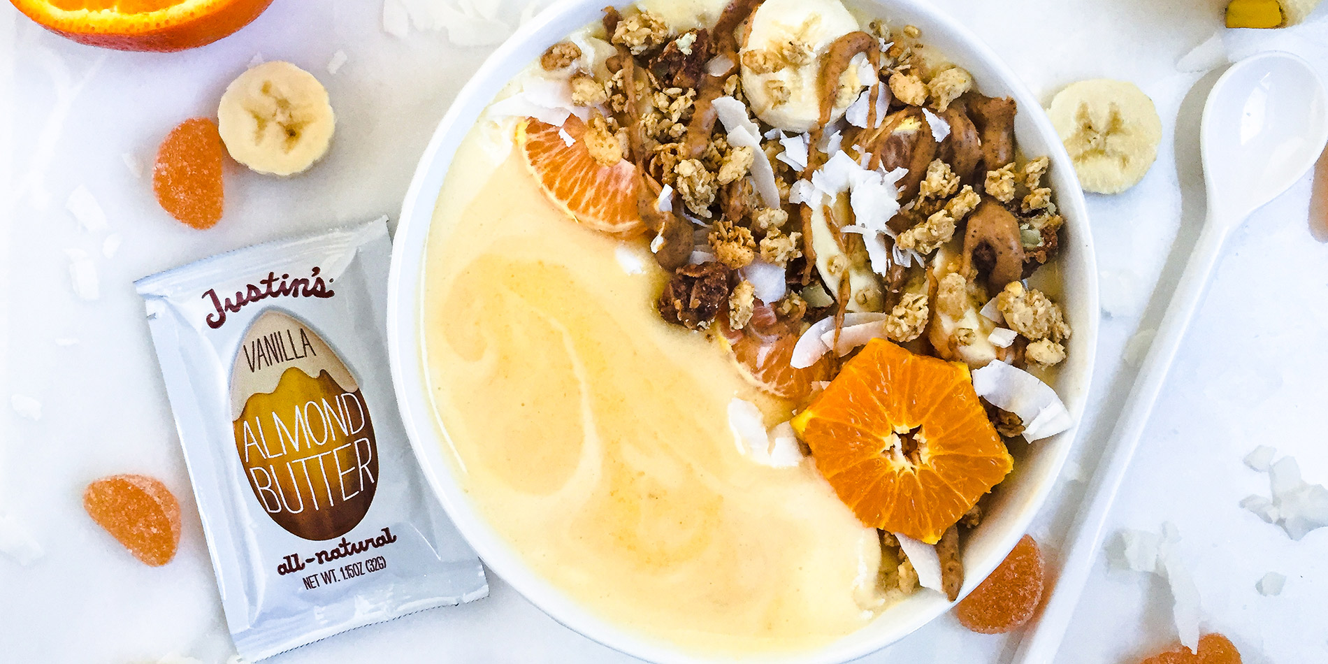 Orange Creamsicle Smoothie Bowl with a sliced orange & banana, with scattered banana slices, orange jelly, and coconut flakes