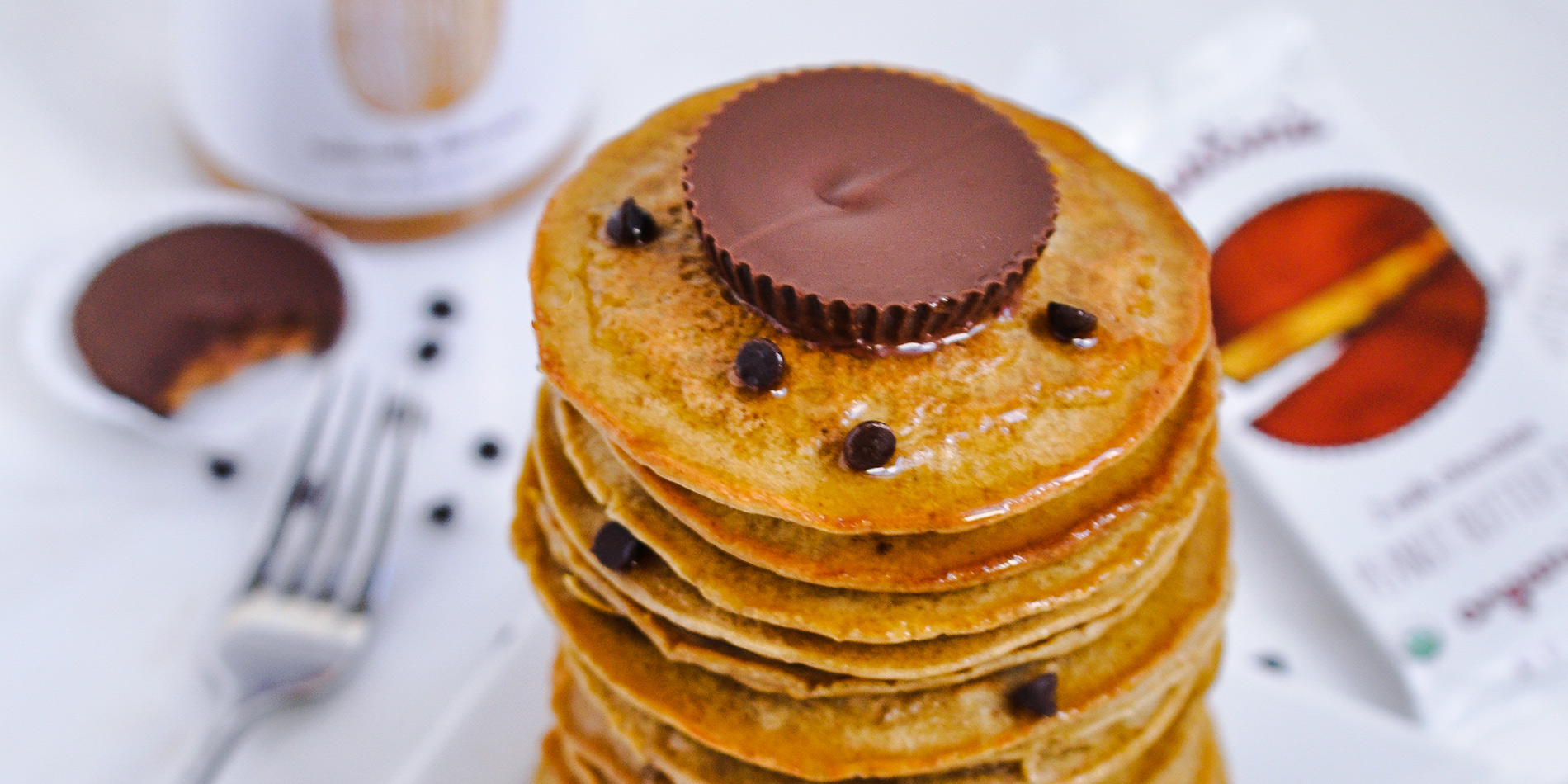 Peanut Butter and Chocolate Chip Protein Pancakes stacked on top with peanut butter cup and chocolate chip sprinkles
