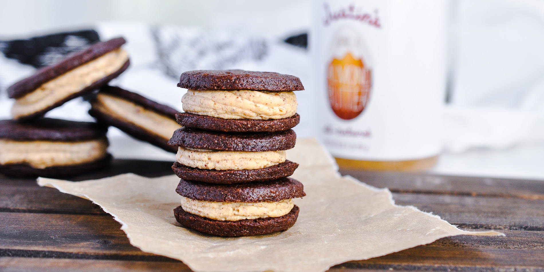 Vanilla Almond Crème Filled Sandwich Cookies stacked on parchment paper with cookies and peanut butter jar in background