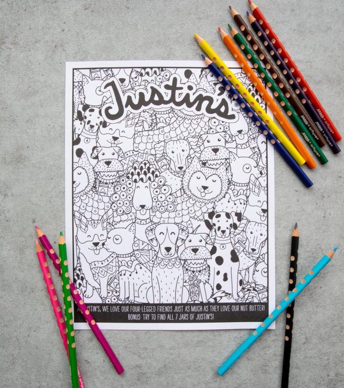 Justin's free printable coloring page with line art of dogs with colored pencils laid out on a grey textured background