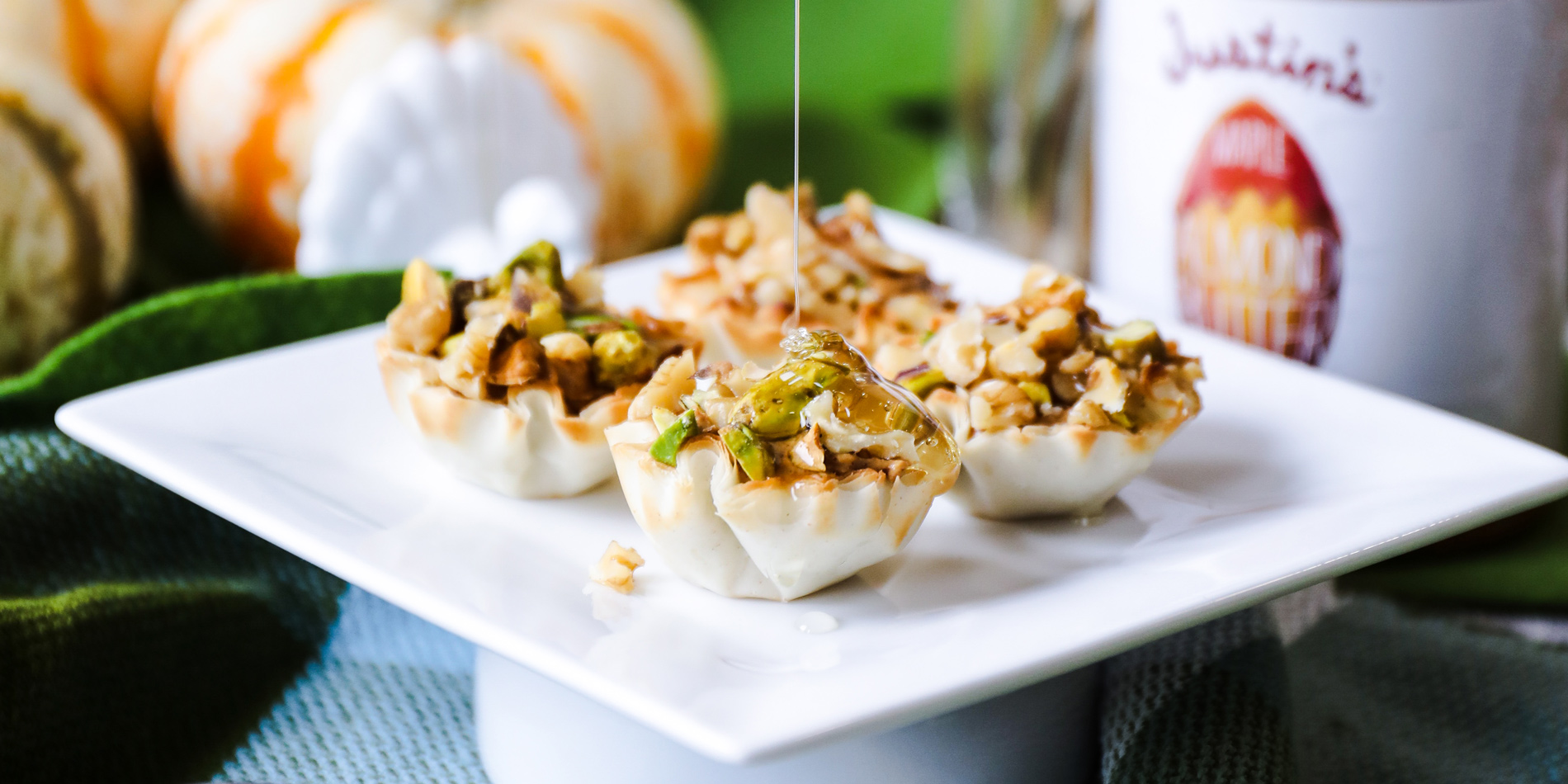 Almond Butter Baklava Bites with honey dripping from top and placed on a white plate and fall decorations in the background