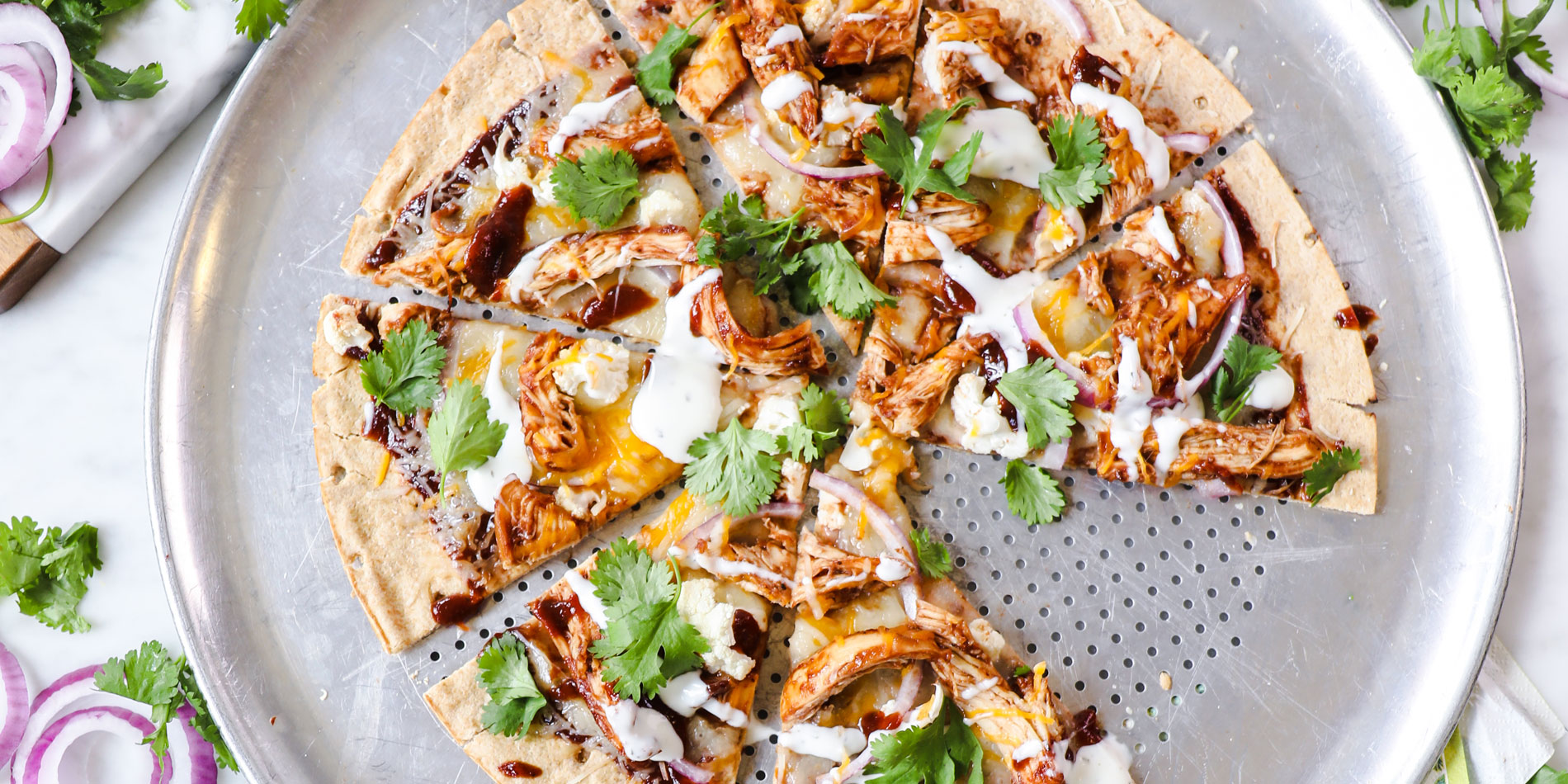 Almond Butter BBQ Chicken Pizza on a round metal pan with one piece on a separate white plate on a white marble background