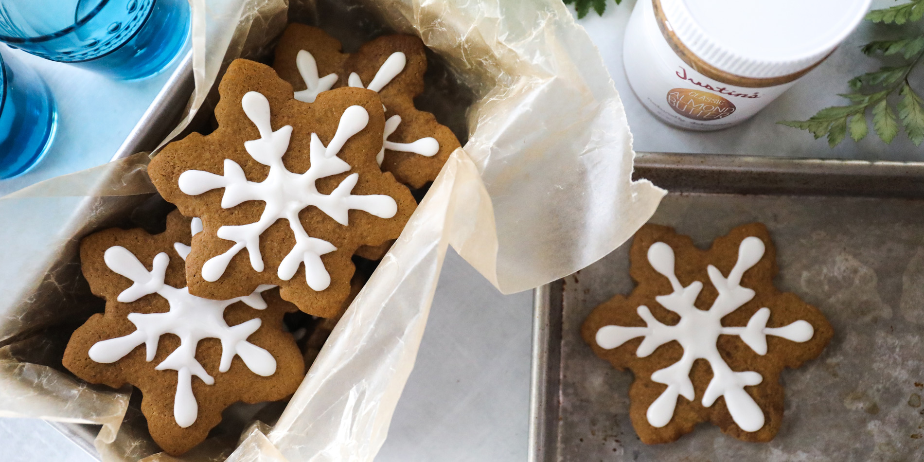 Almond Butter Gingerbread Cookies in snowflake shape on parchment paper in a pan on a white background