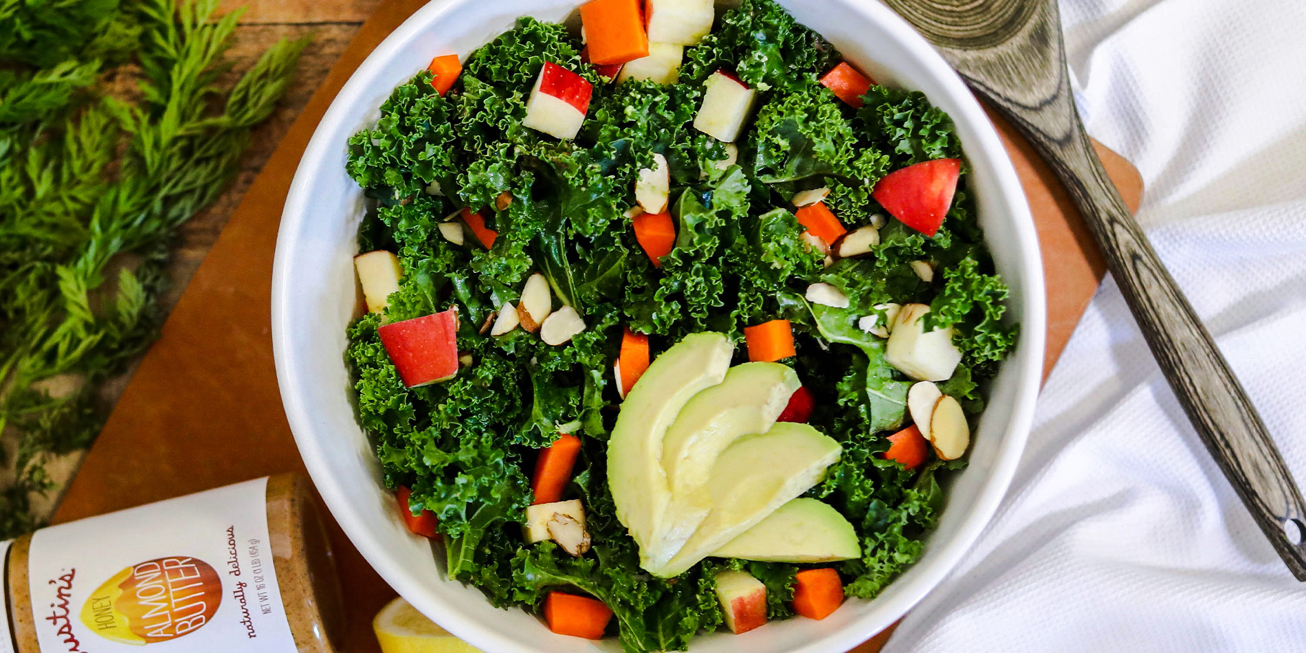 Massaged Kale Salad with Honey Almond Butter Vinaigrette in a white bowl with carrots and cut lemons in the wood background