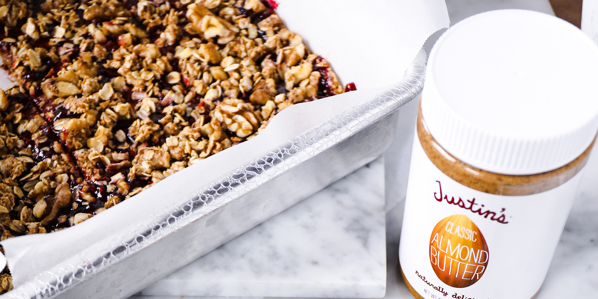 No-Bake Almond Butter and Jelly Breakfast Squares on a white tray with a jar of JUSTIN'S® Classic Almond Butter on the side thumbnail image.