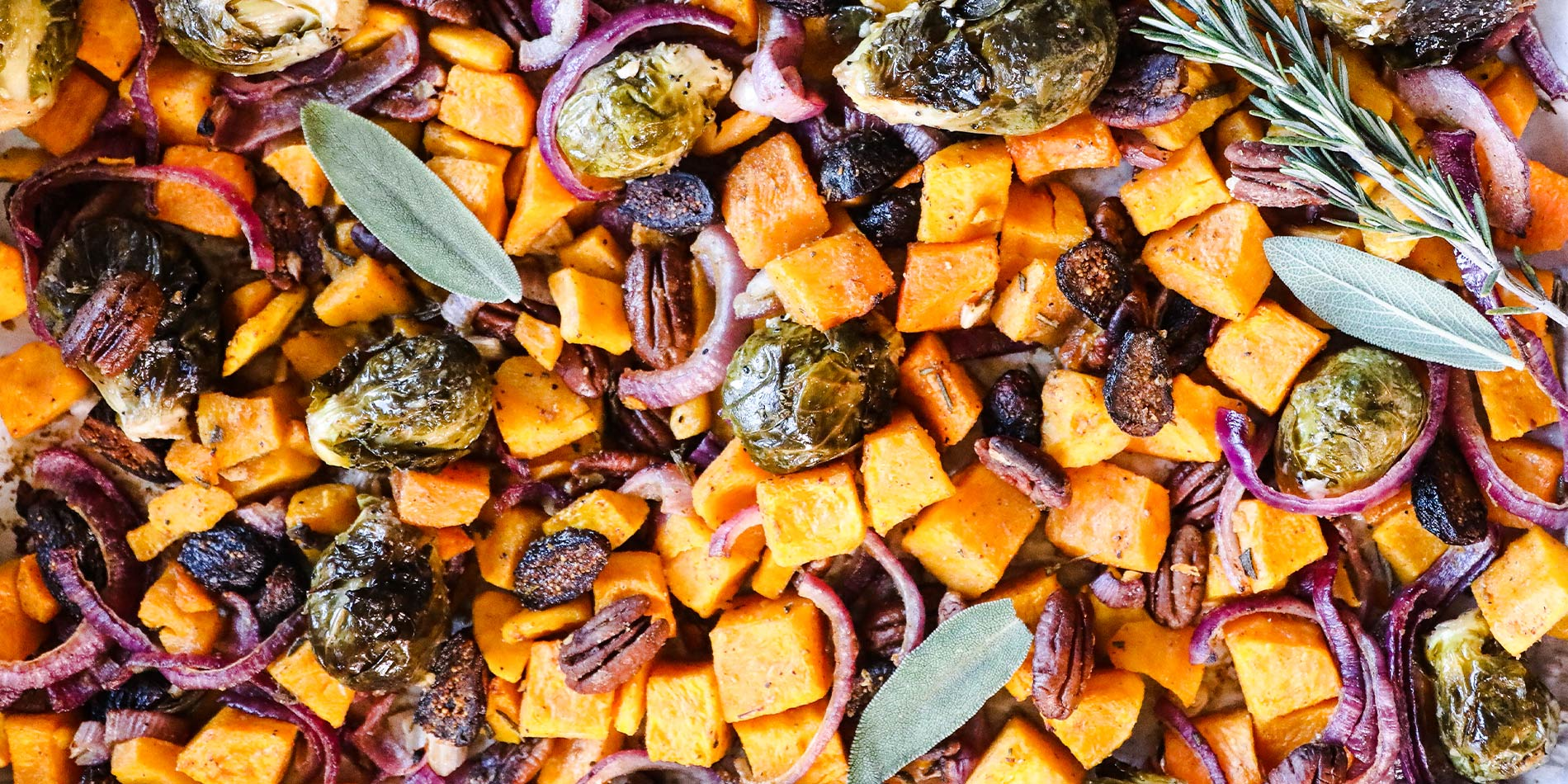 Nutty Butternut & Brussels Hash in a tray with parchment paper on a white background with golden fork and knife