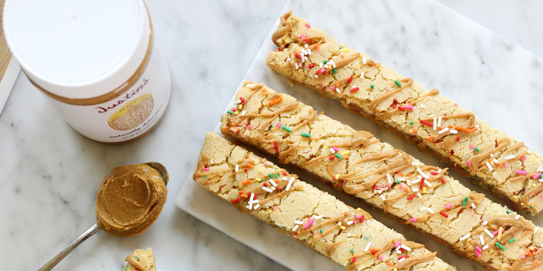 Gluten-Free Peanut Butter Biscotti on a white plate and marble tray with coffee on a white marble background