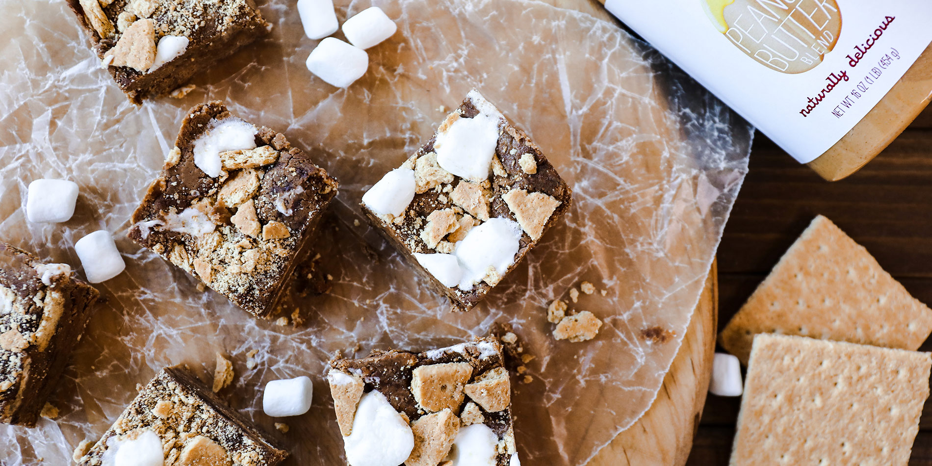 Peanut Butter S'mores Protein Fudge on square-cut crumpled clear parchment paper on a wood tray with a darker wood background