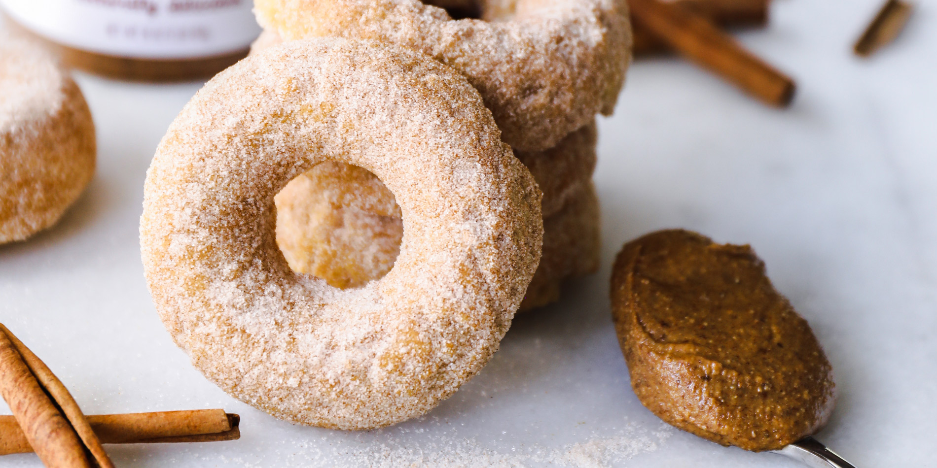 Baked Cinnamon Almond Butter Churro Doughnuts with cinnamon sticks in the background on a white background