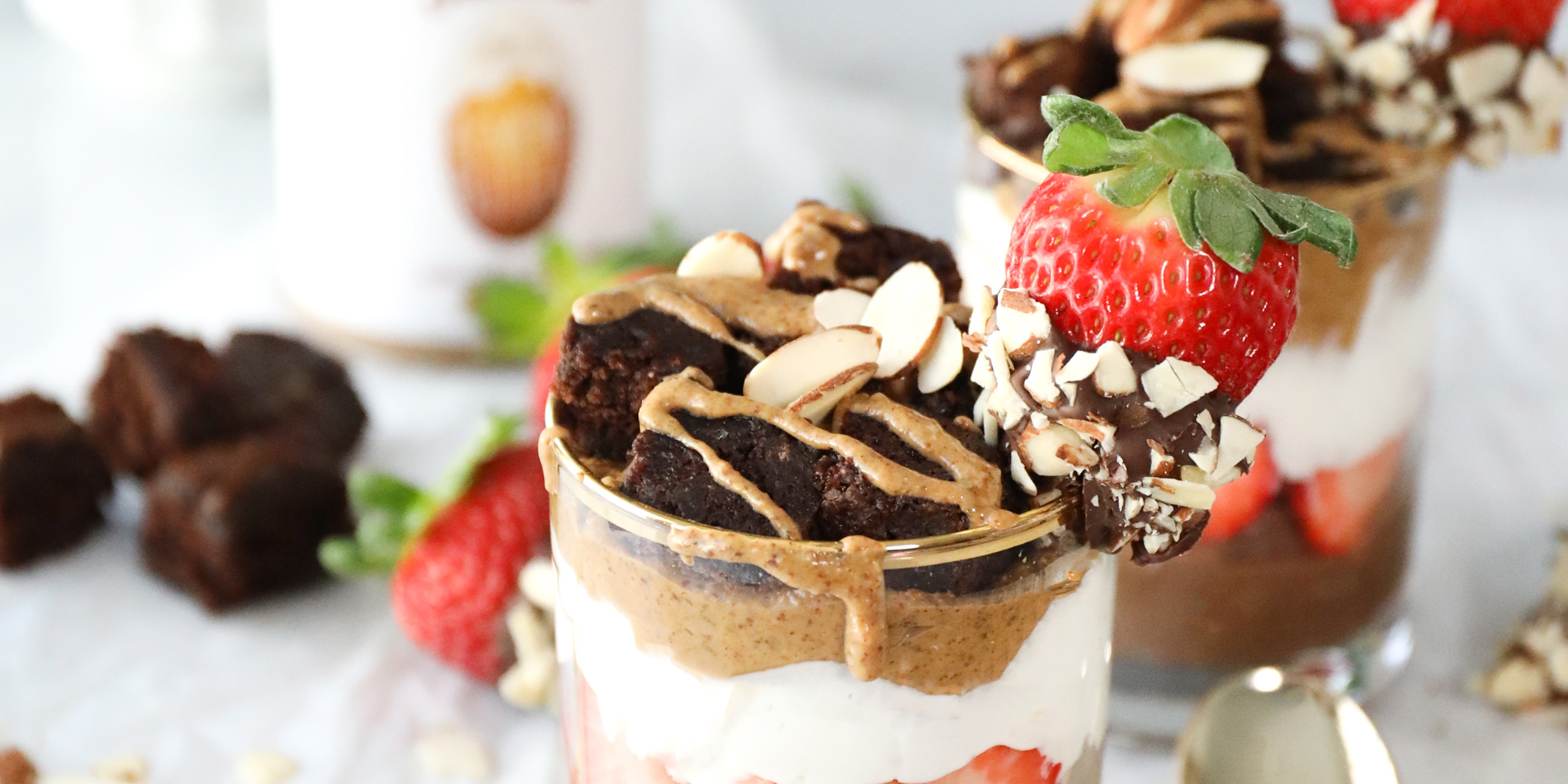 Chocolate Covered Strawberry and Almond Butter Parfait with gold spoons and chocolate fudge chunks in a white tabletop