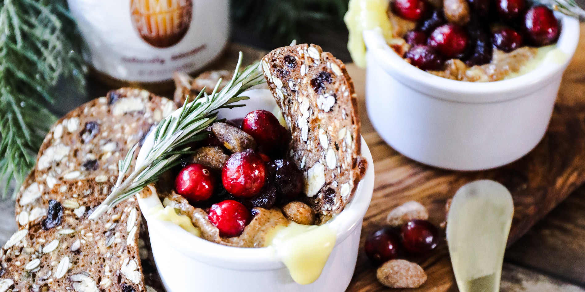 Cranberry Almond Butter Baked Brie in a small cup on a wooden serving tray with cranberries and pine on a wood background