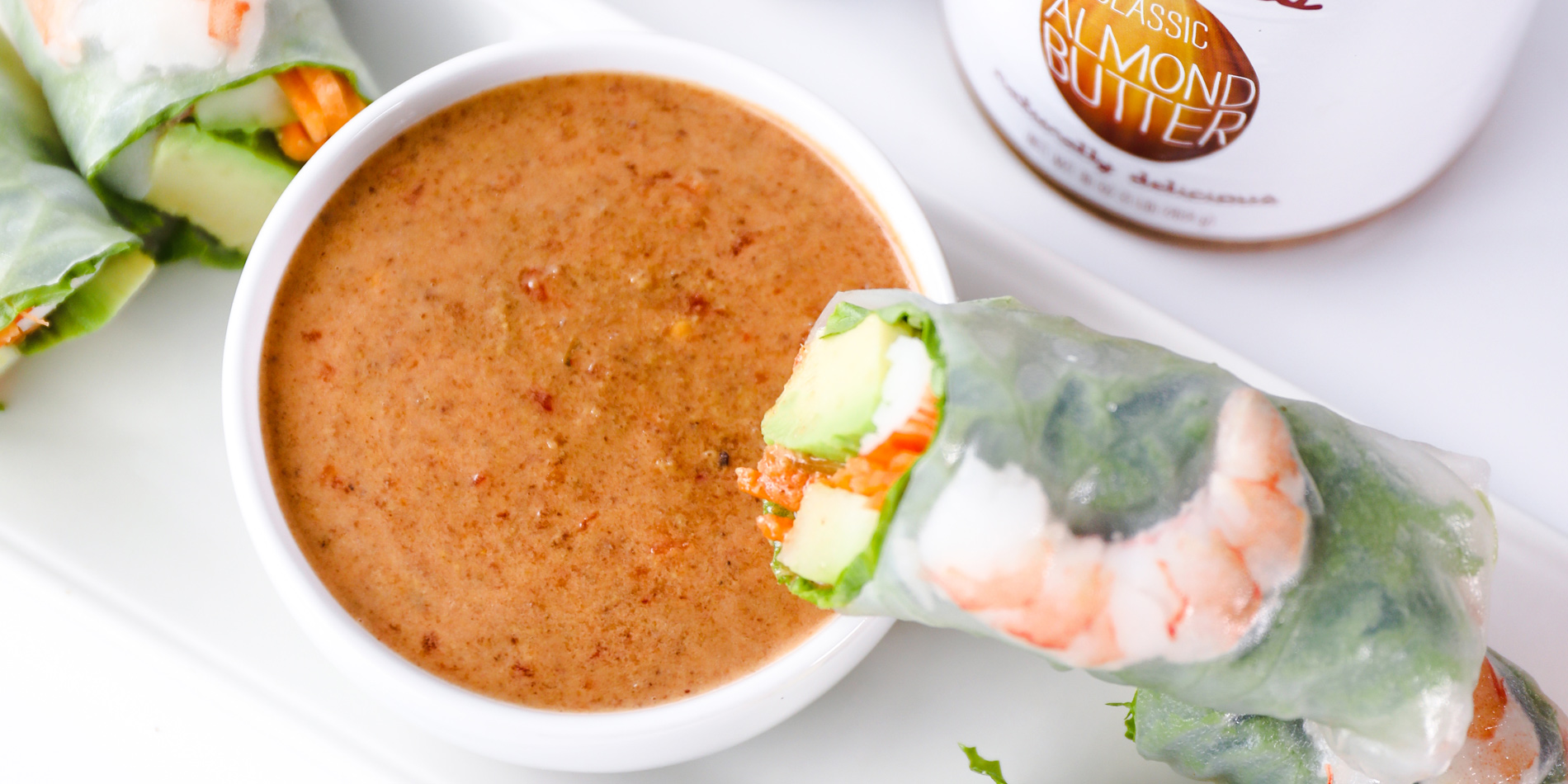 Ginger Almond Sauce with Vietnamese shrimp fresh rolls on white plate with ginger and peanut butter jar in white background