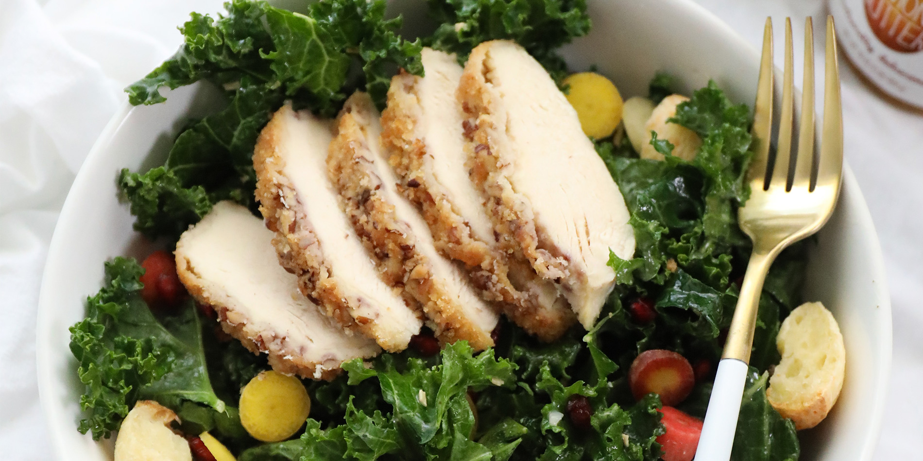 Kale Salad with Almond Butter Crusted Chicken on a white bowl with a golden fork on a white cloth on a white top