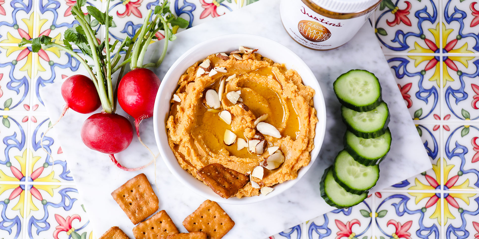 Sweet Potato Almond Hummus on a white bowl with cucumber slices, beets, crackers on a floral patterned tile background
