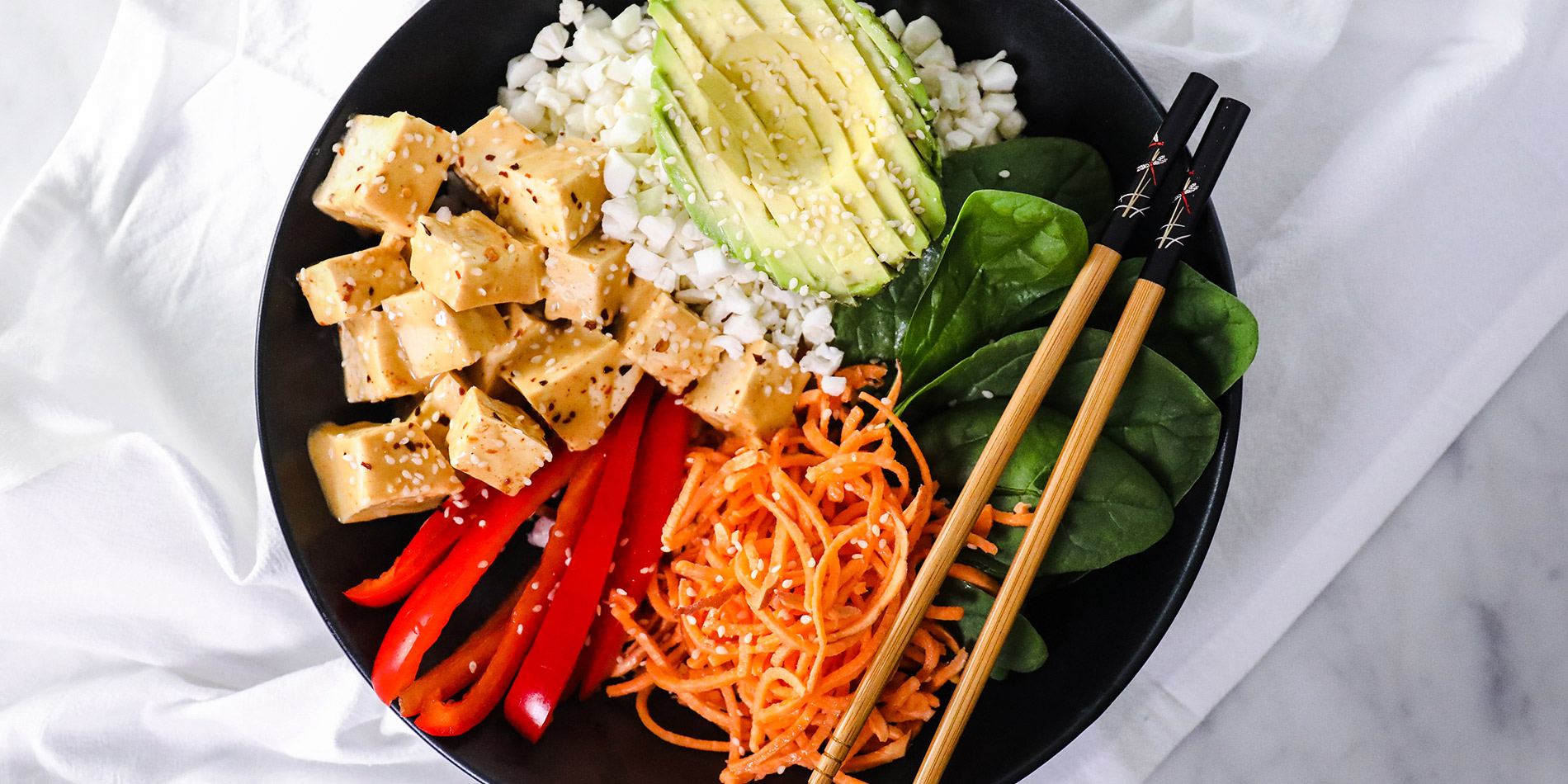Thai Peanut Tofu Bowl in a black bowl with chopsticks from the top view on a white background with a white cloth