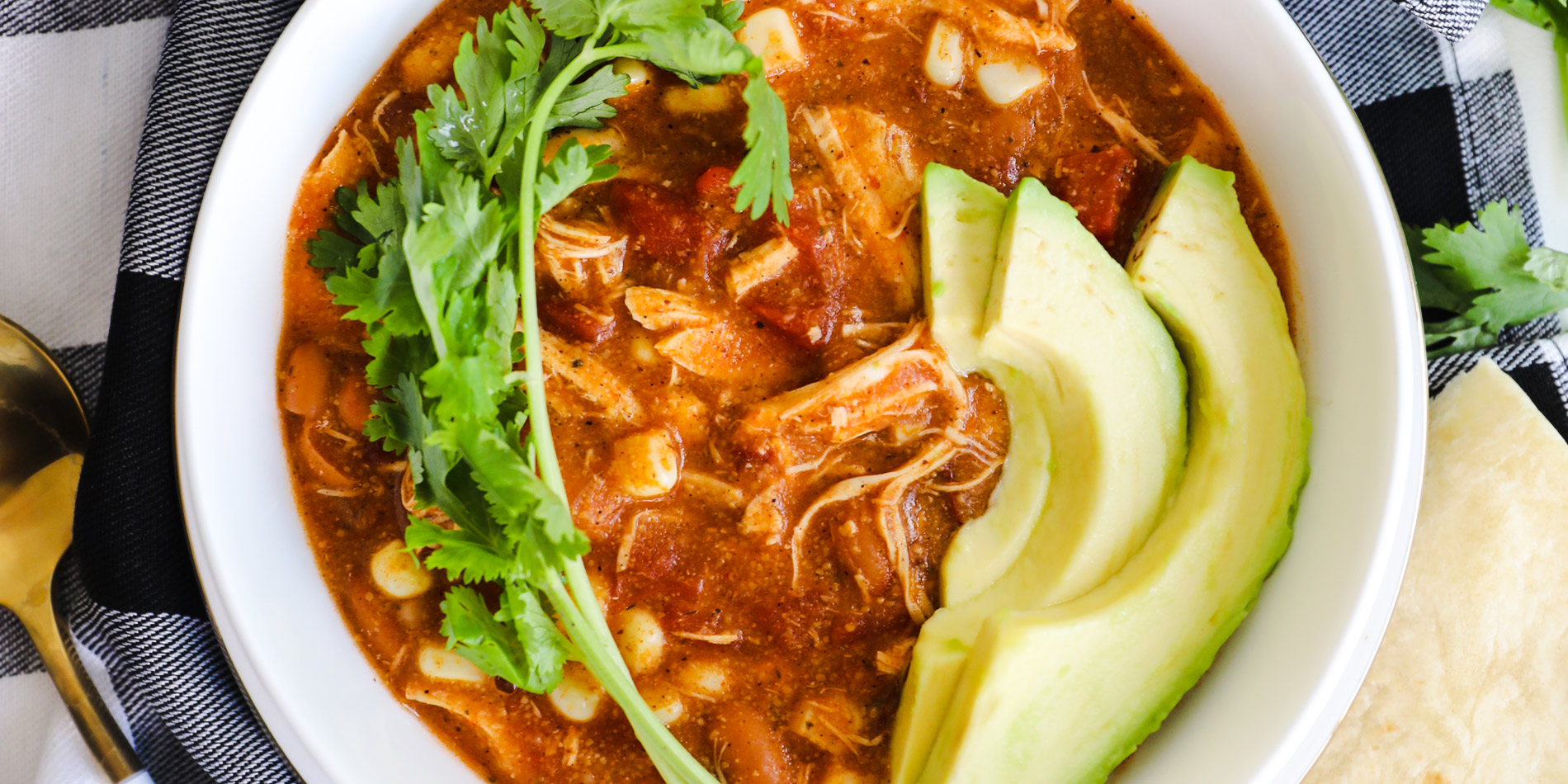 Chipotle Chicken Enchilada Soup in a white bowl with avocado and cilantro and tortillas on a checkered cloth