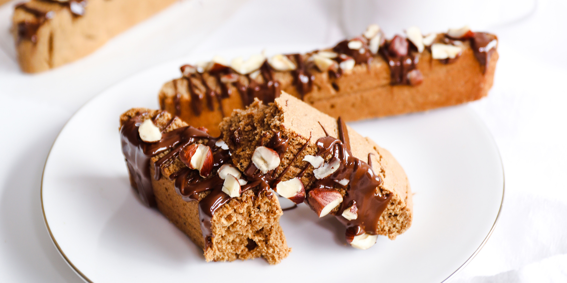 Chocolate Hazelnut Espresso Biscotti on a white plate with silver lining beside a cup of coffee in a white background
