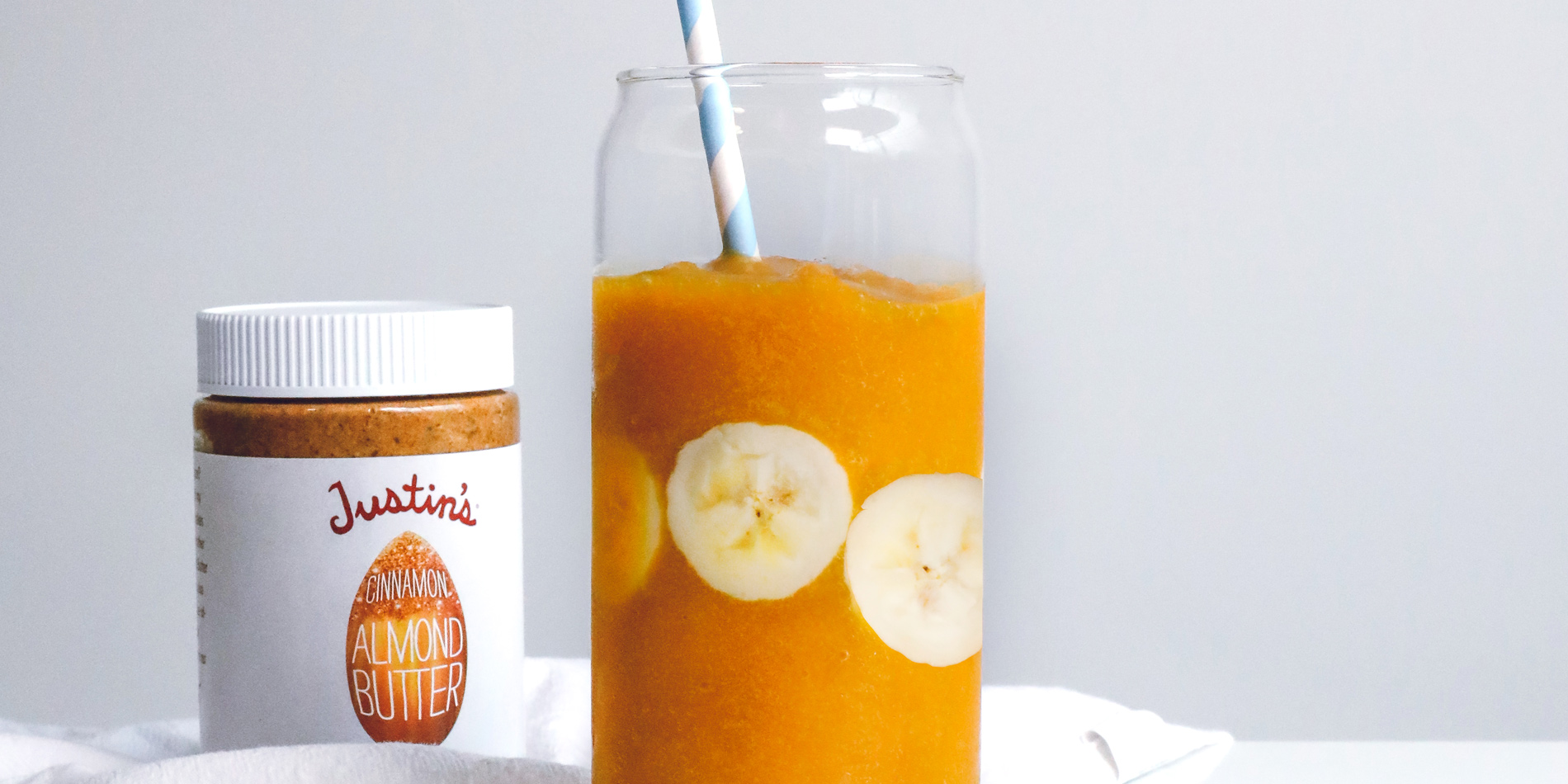 Golden Cinnamon Turmeric Smoothie with banana slices with a straw in a clear cup in a white background with a white cloth