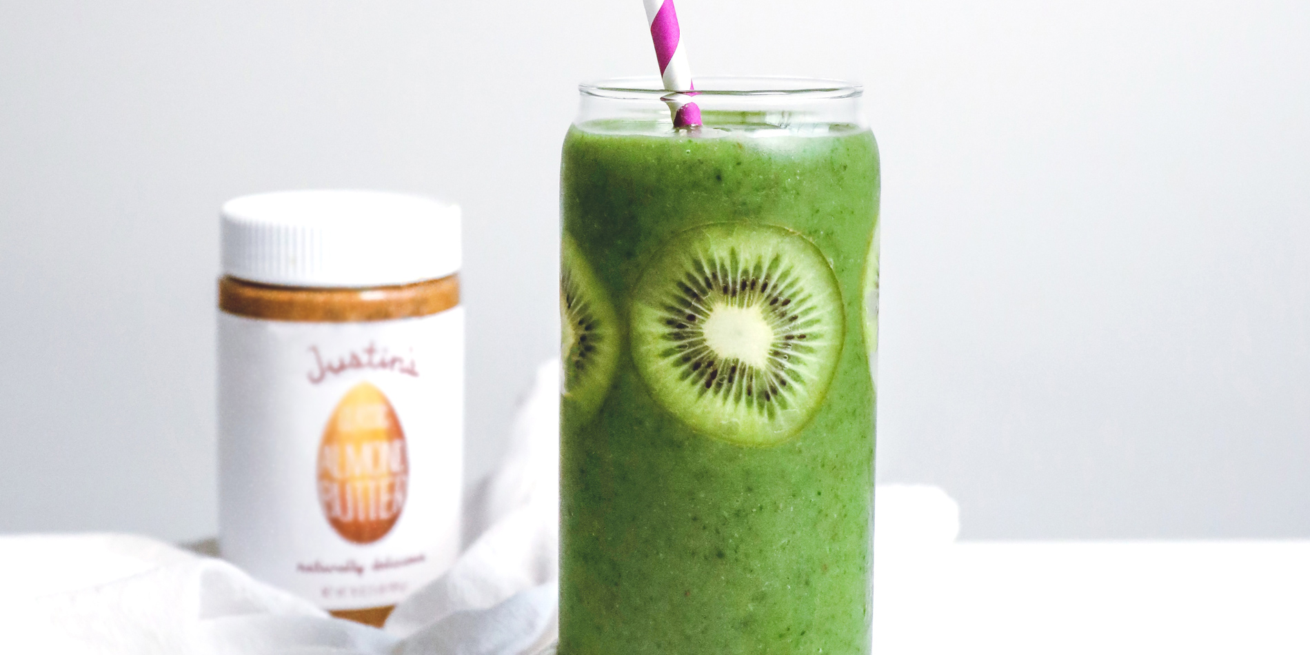 Justin's Ultimate Green Drink in a clear cup with a striped straw with kiwis on a white background