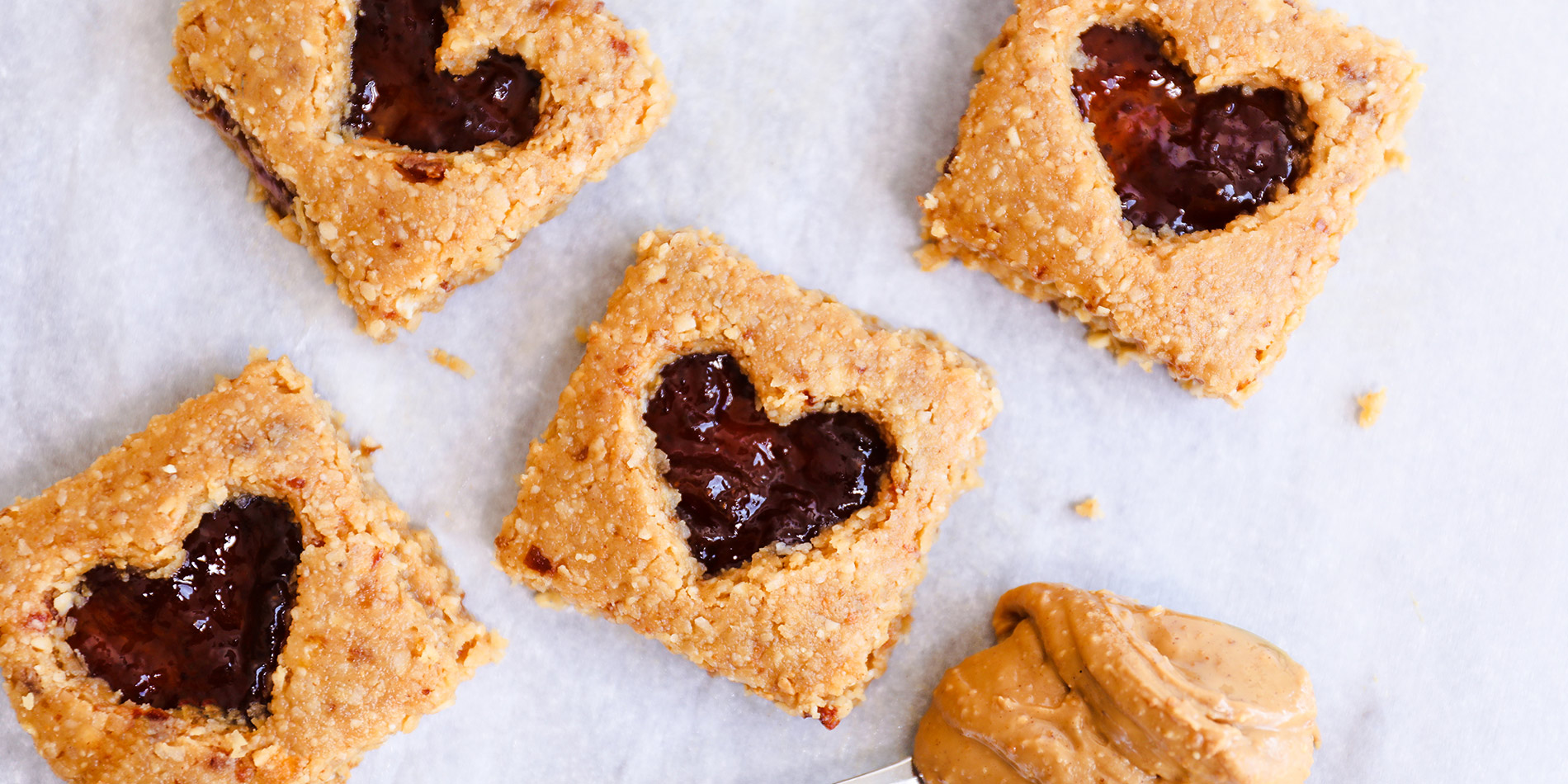 No Bake PB & J Bars with heart-shaped jelly center with a spoonful of peanut butter on white background with crumbs