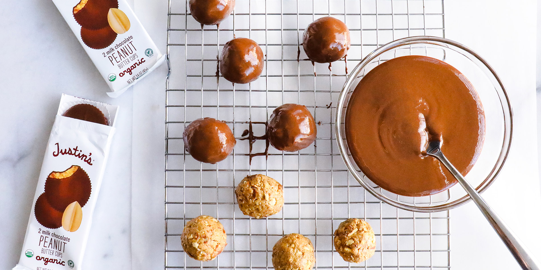 Peanut Butter Pretzel Balls on a cooling tray with 2 peanut butter cup packs on the left on a white marble background