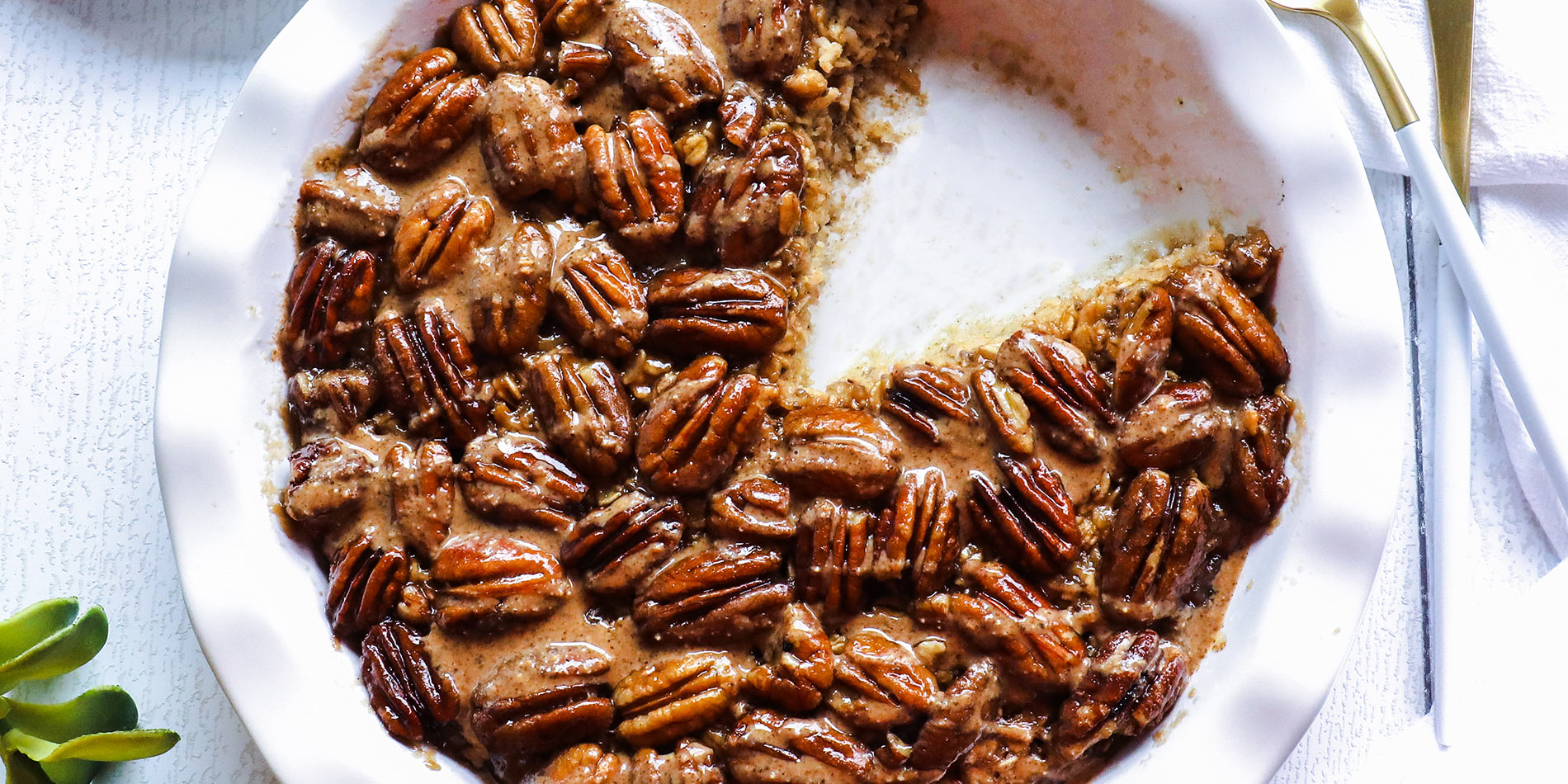 Pecan Pie Baked Oatmeal with Cinnamon Almond Butter in a white bowl with a slice cut out on separate dish on white background