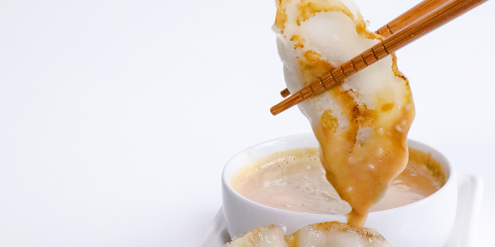 Spicy Peanut Sauce used to dip dumplings being held with brown wooden chopsticks on a white background