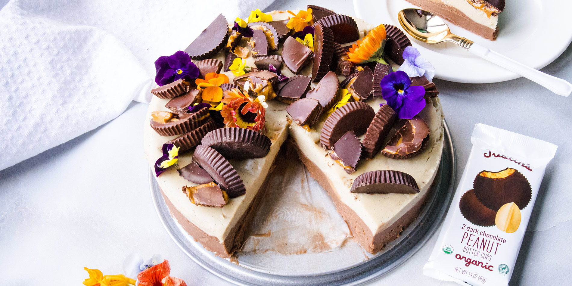 Peanut Butter Chocolate Cashew Cheesecake on a gray tray with a slice taken out and placed on top right side of the photo