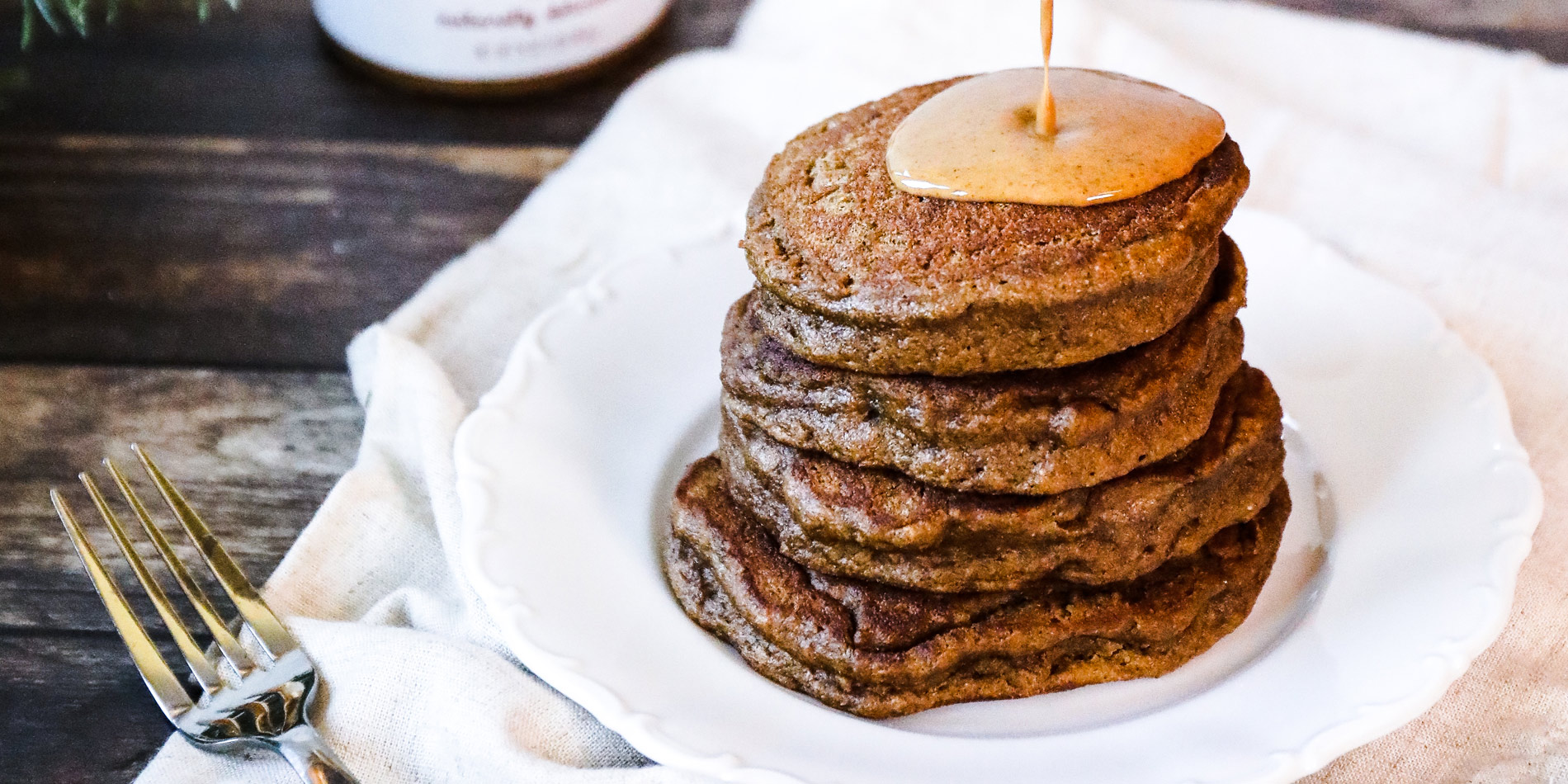 Gingerbread Almond Butter Pancakes with peanut butter drizzle on a white plate with wooden background with pine tree