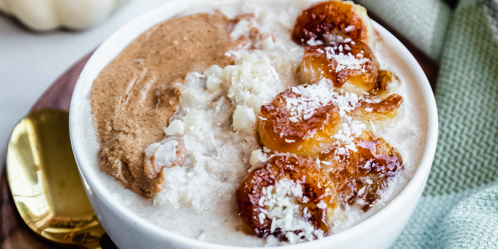 Grain Free Coconut Cauliflower Oats with Caramelized Bananas on a wood bowl with a gold spoon on a white background