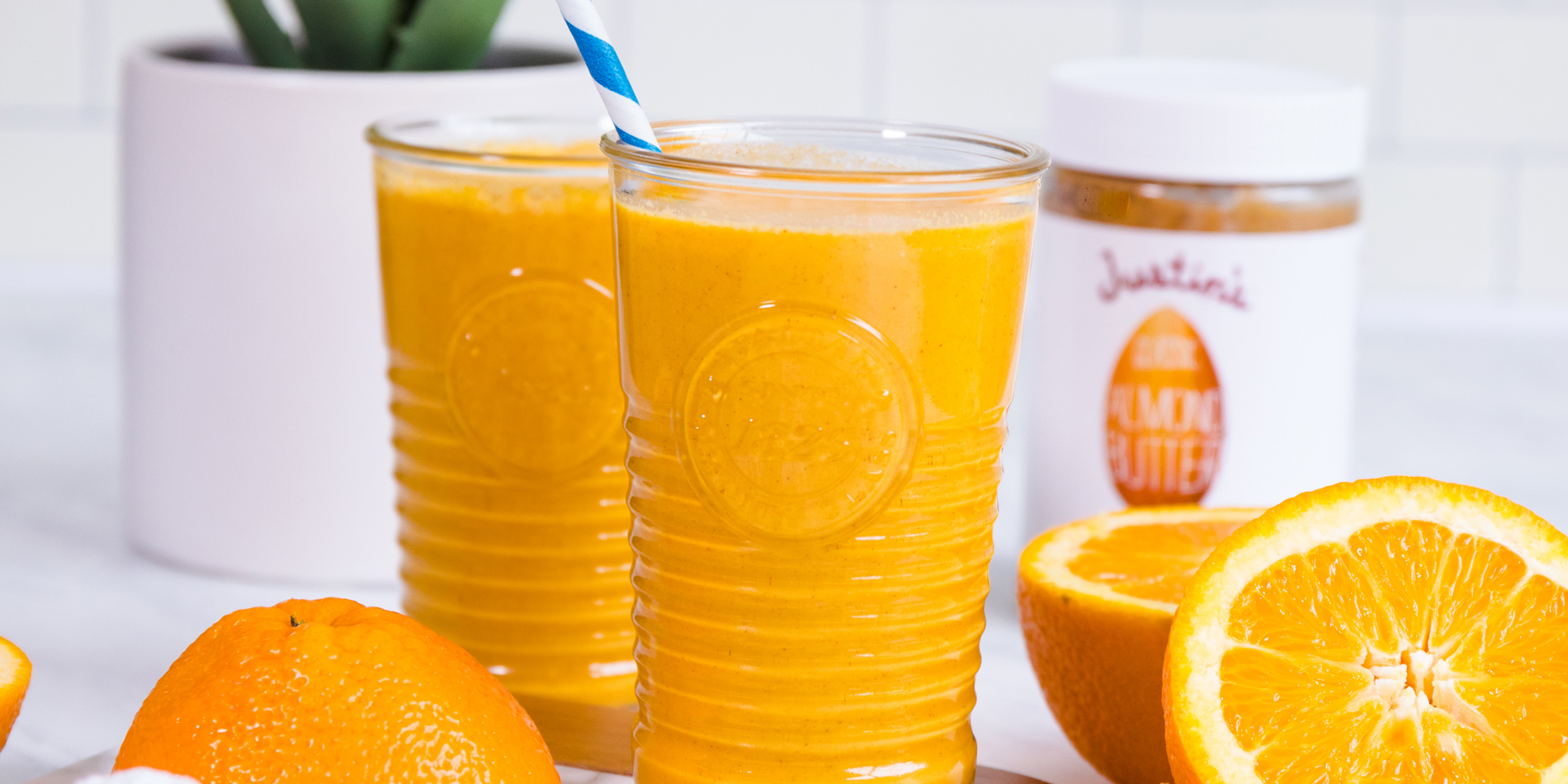 Orange Creamsicle Smoothie in tall glass cups with a white and blue straw with oranges in the background