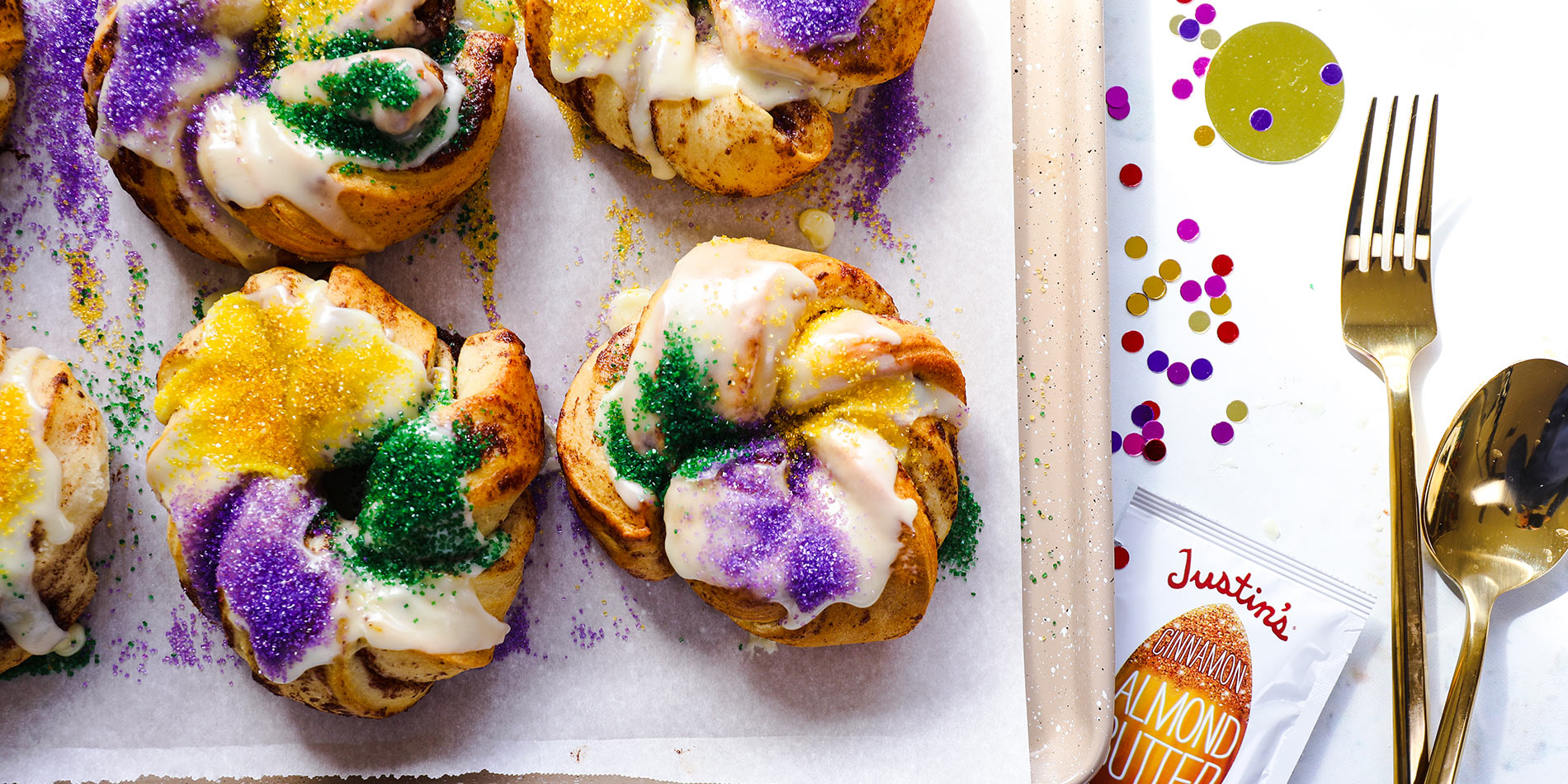 Personal Cinnamon Almond Butter King Cakes on top of a tray with parchment paper with rainbow confetti on a white background
