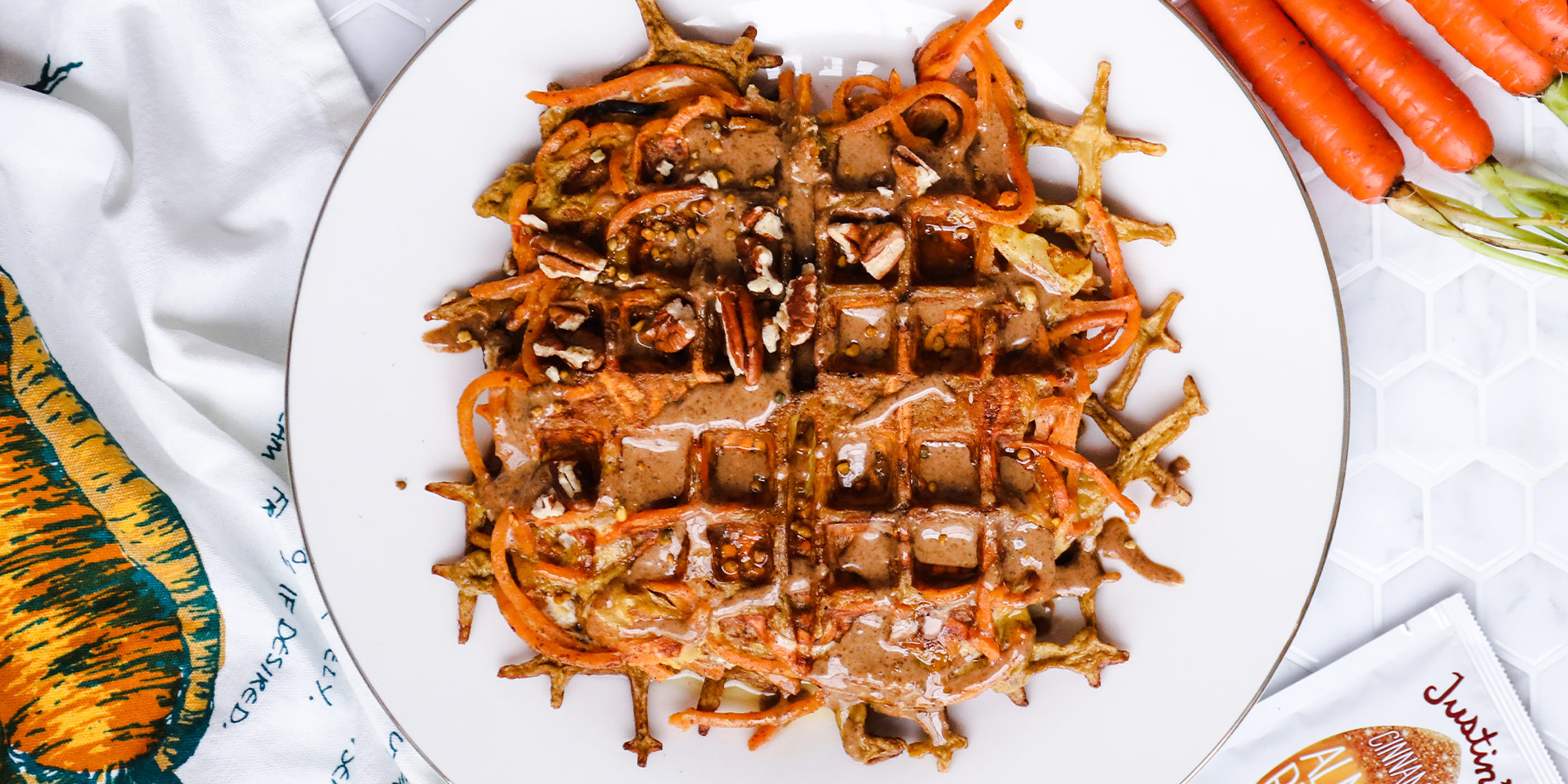 Spiralized Carrot Cake Waffle with carrots and a gold fork in the white tile background with a cloth with carrot illustration