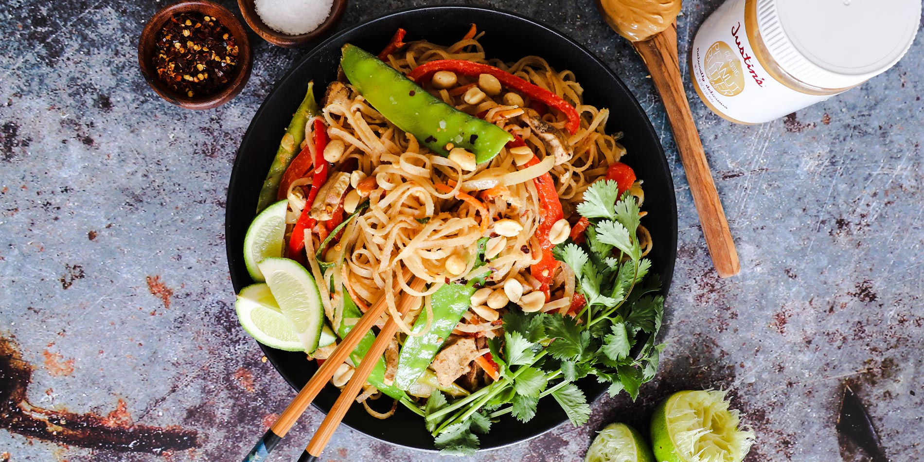 Thai Peanut Noodles in a black bowl with a spoonful of peanut butter on the side on a gritty gray background with lime slices