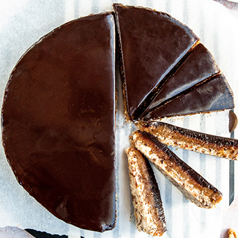 Almond Caramel Tart sliced and rotated for display over parchment, on a striped tabletop (thumbnail)