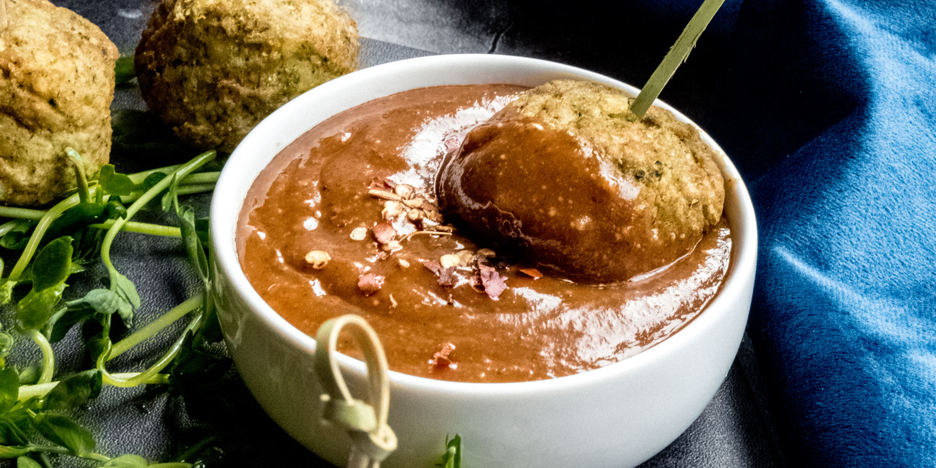 Balsamic Almond Butter Dipping Sauce dipped with meatballs in a small round white bowl against a blue fabric background